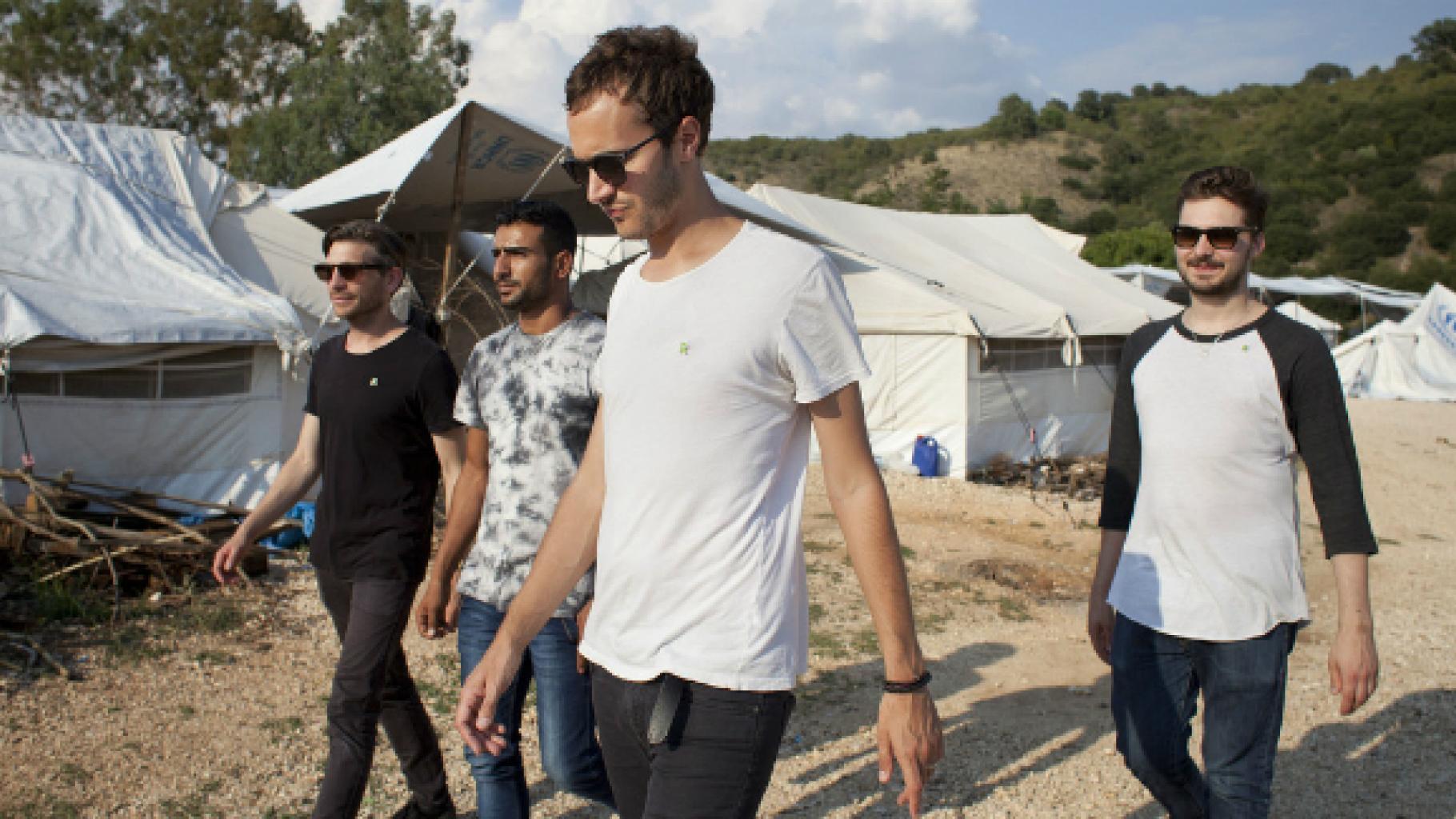Mitglieder der Band Editors laufen durch ein Flüchtlingscamp in Griechenlands