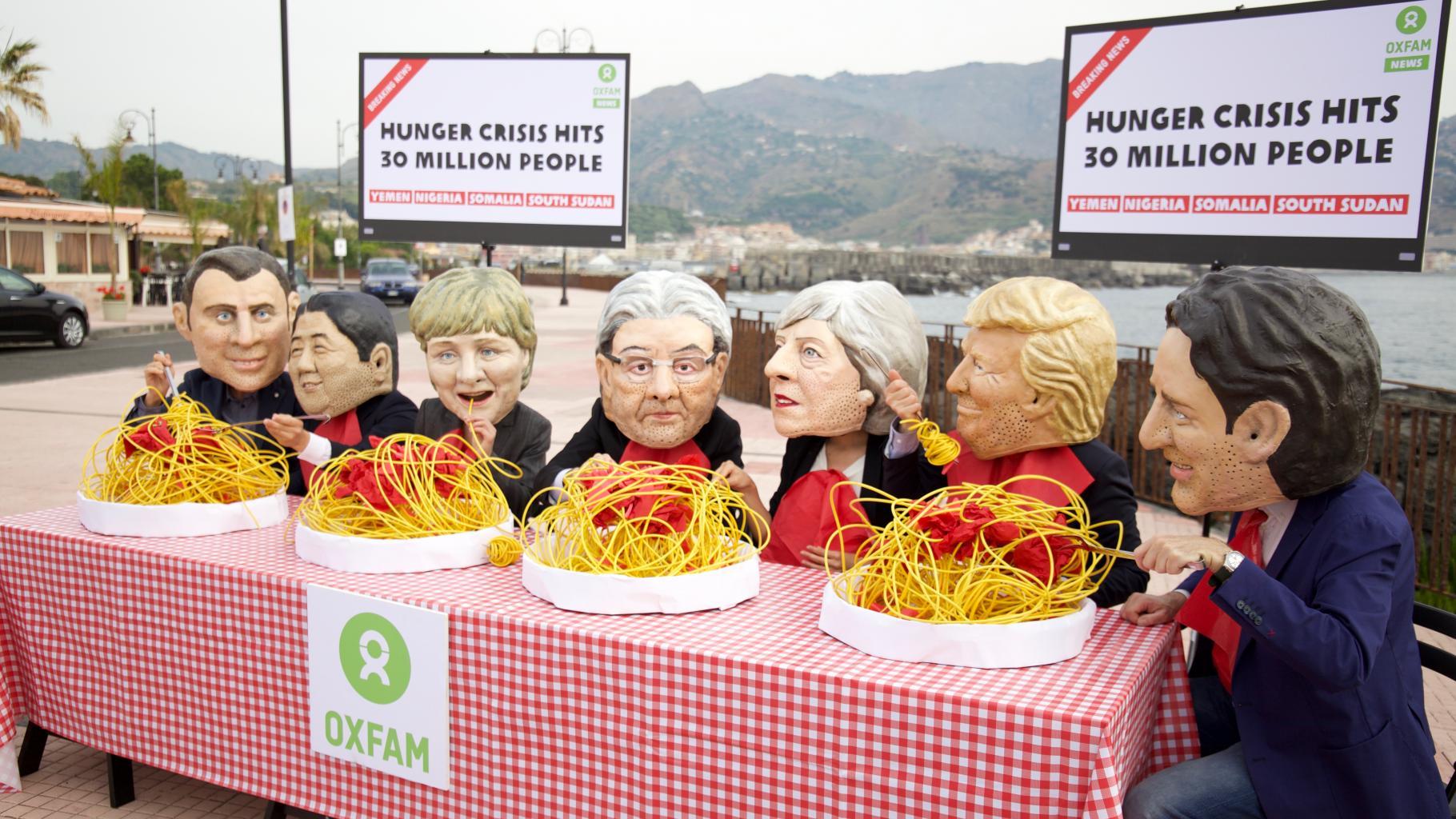 """Aktivist/innen mit Masken der Staats- und Regierungschefs essen Spaghetti, während im Hintergrund auf Fernsehern die Meldung erscheint: """"Hunger crisis hits 30 million people – Yemen, Nigeria, Somalia, South Sudan"""""""