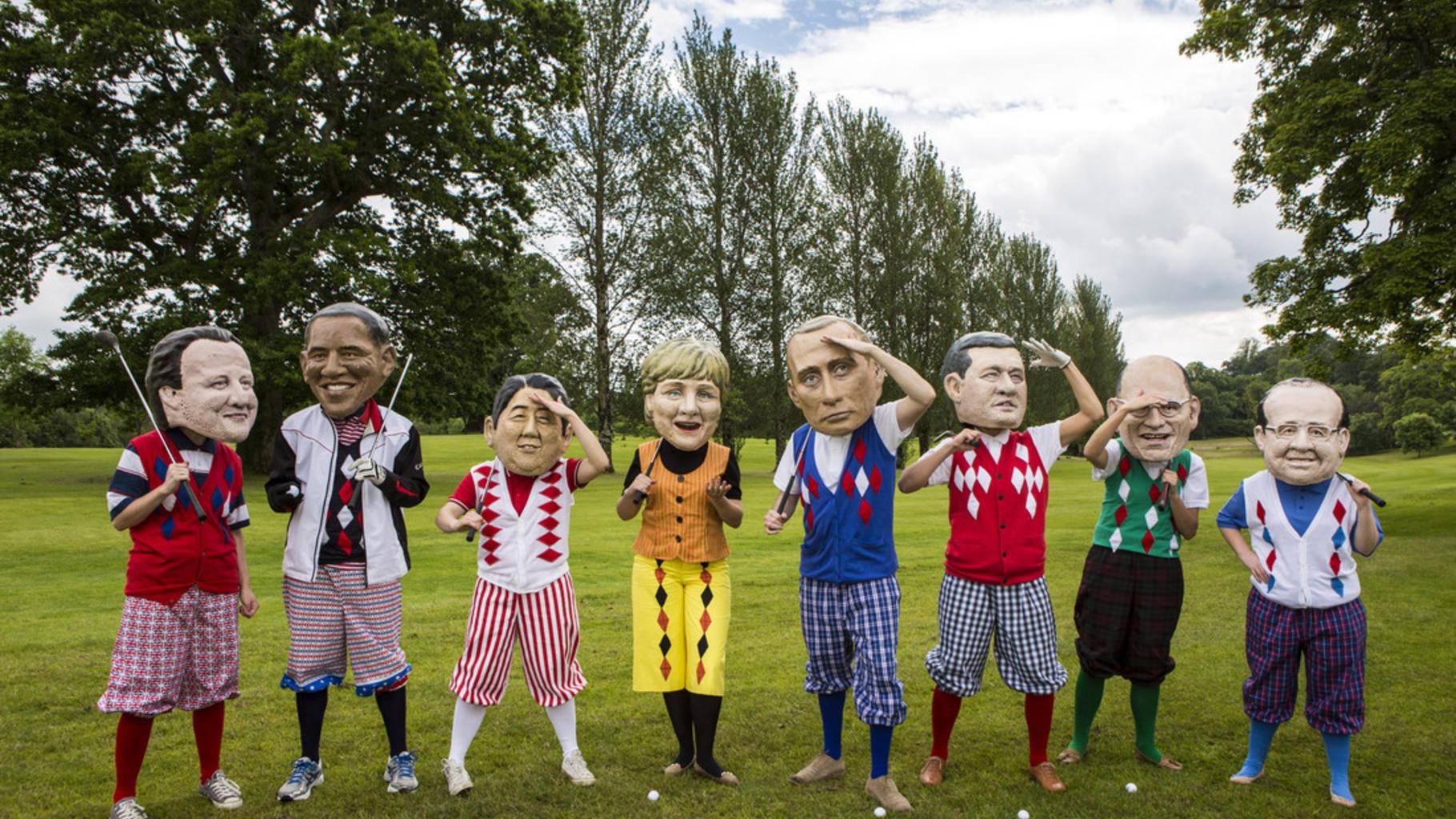 G8-Politiker - dargestellt mit großen Masken - in Golfkleidung