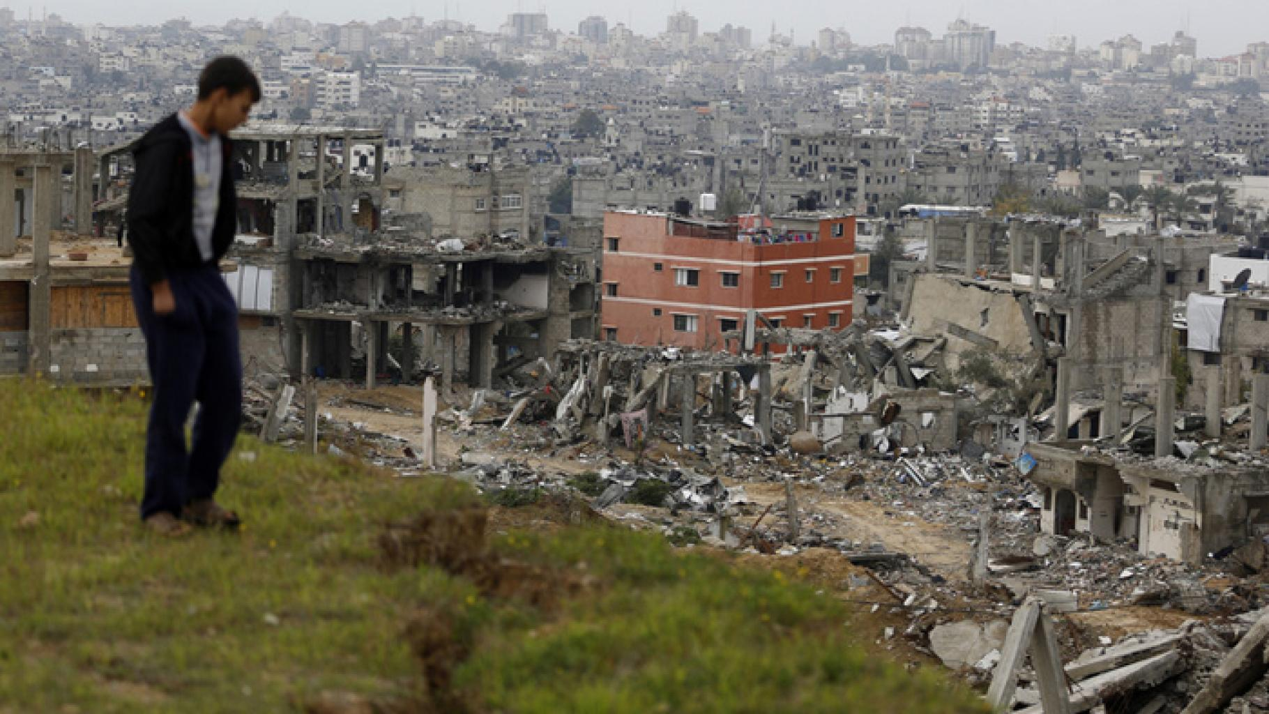 Ein Mann blickt von einem Hügel auf eine zerstörte Stadt herab.