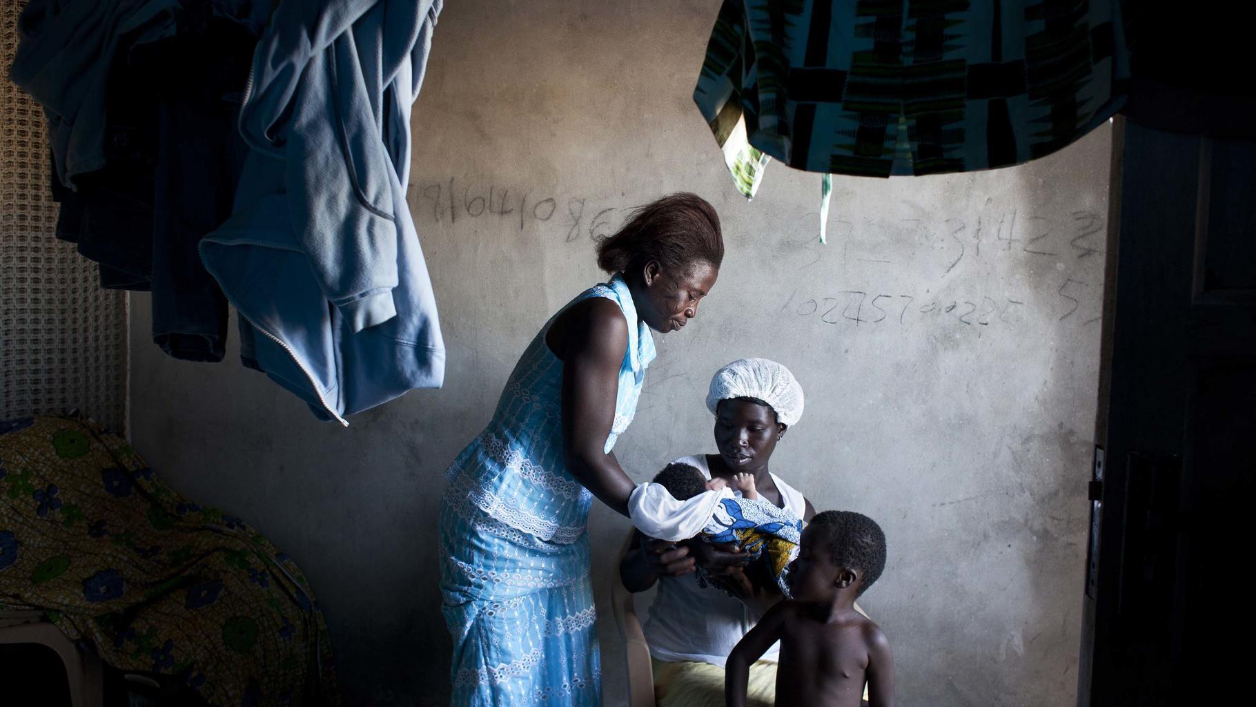 Zwei Frauen halten ein neugeborenes Baby
