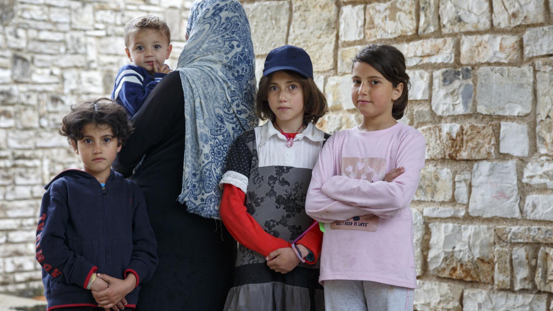 Eine Frau wendet der Kamera ihren Rücken zu; sie hält ein Kind auf dem Arm, das in die Kamera blickt. Neben ihr stehen drei Kinder in selbstbewusster Haltung, die mit entschlossenem Gesichtsausdruck in die Kamera blicken.