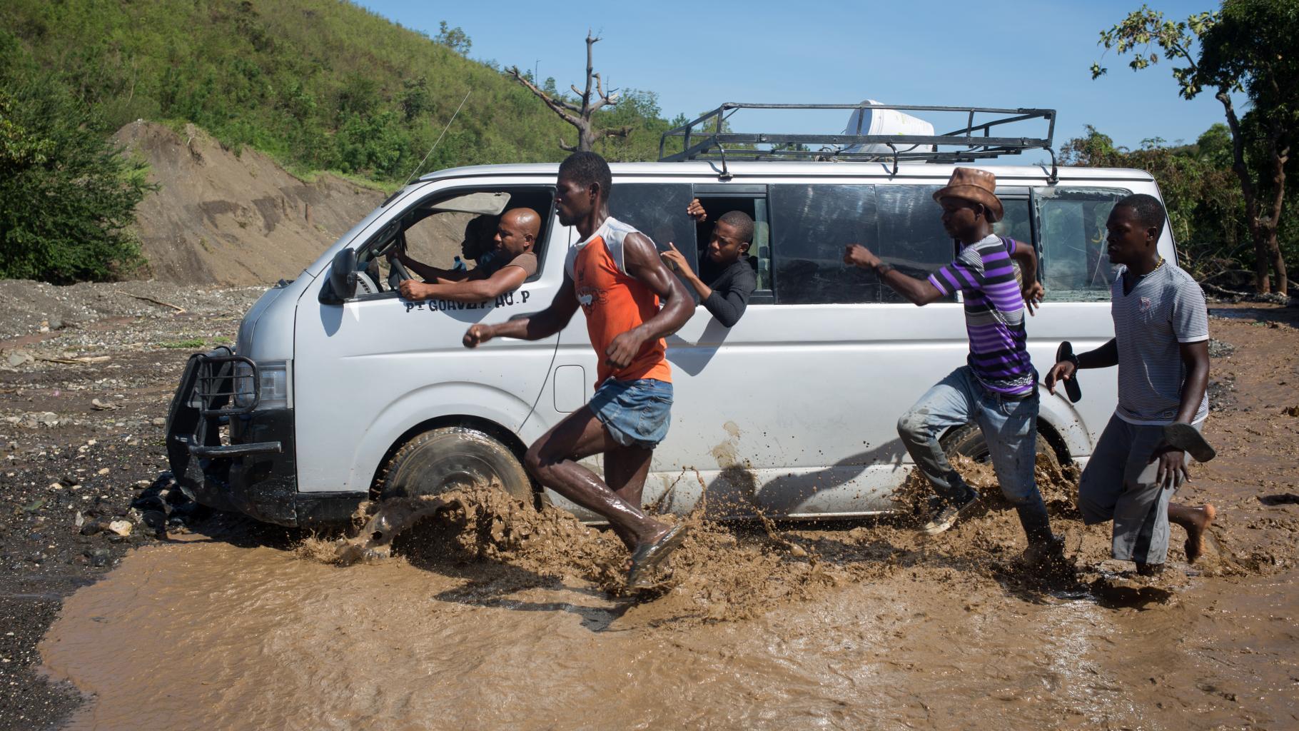 Ein weißer Transporter fährt durch einen Fluss ans Ufer, während einige Männer nebenher durch das Wasser rennen.