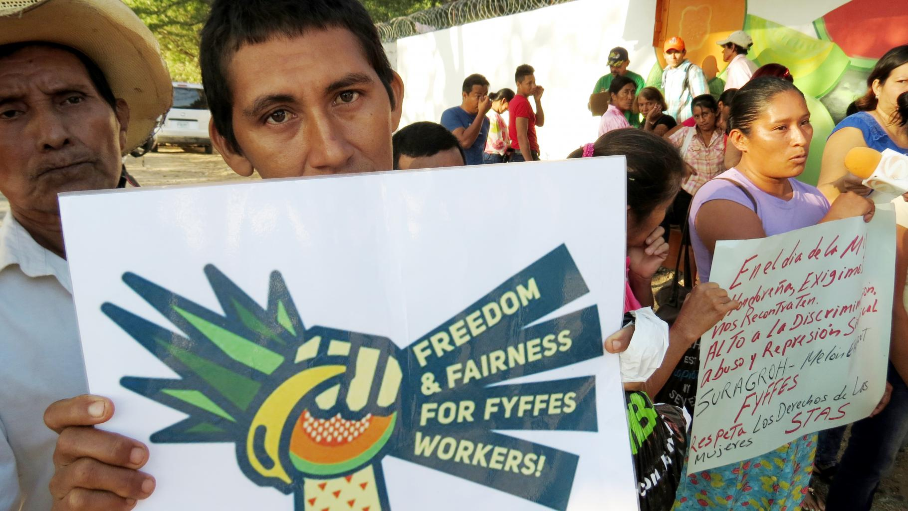 "Ein Demonstrant hält ein Plakat in die Kamera: ""Freedom and fairness for Fyffes workers!"""