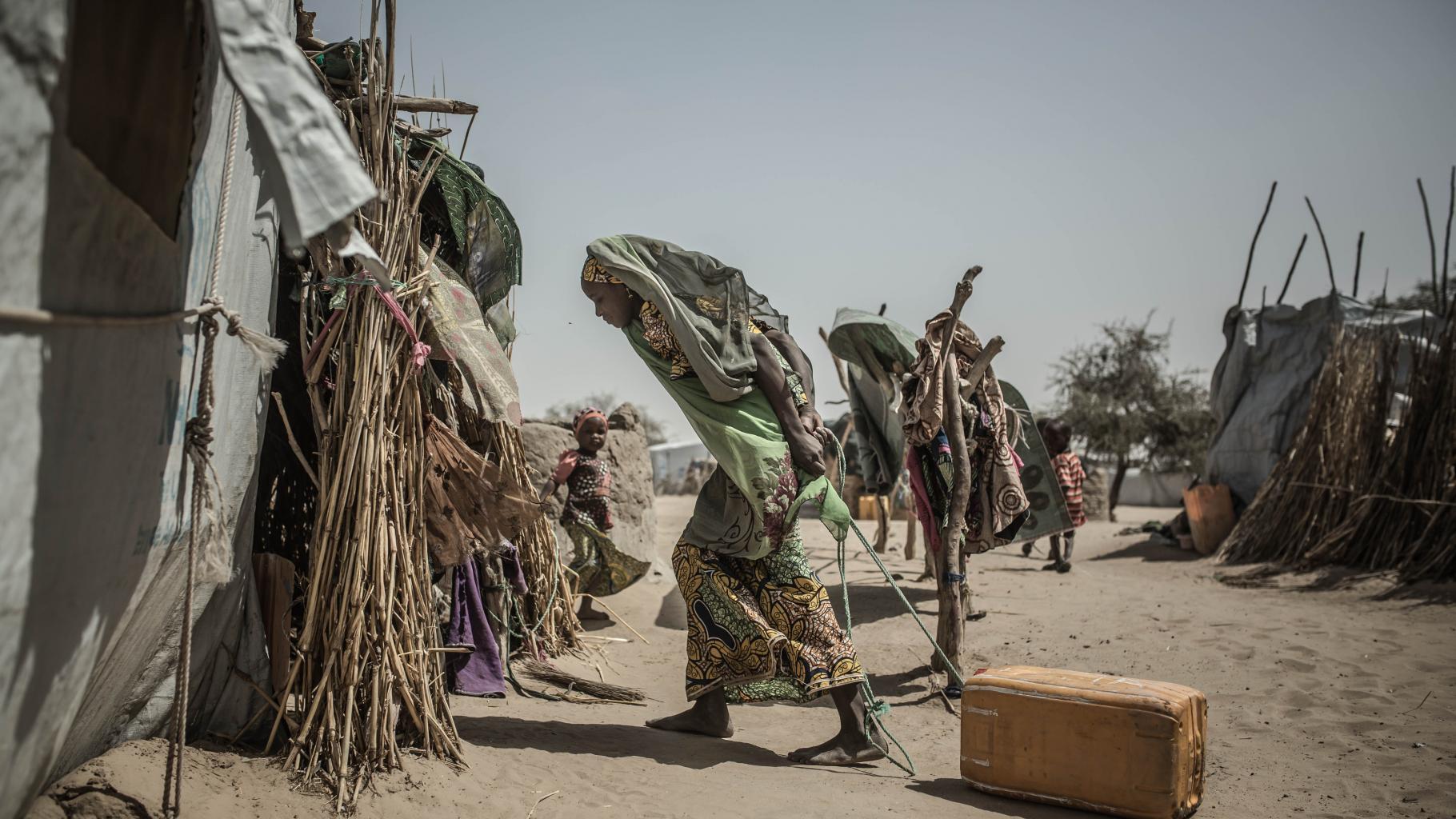 Eine Frau zieht einen Wasserkanister an einem Strick hinter sich durch den Sand in ein Zelt.