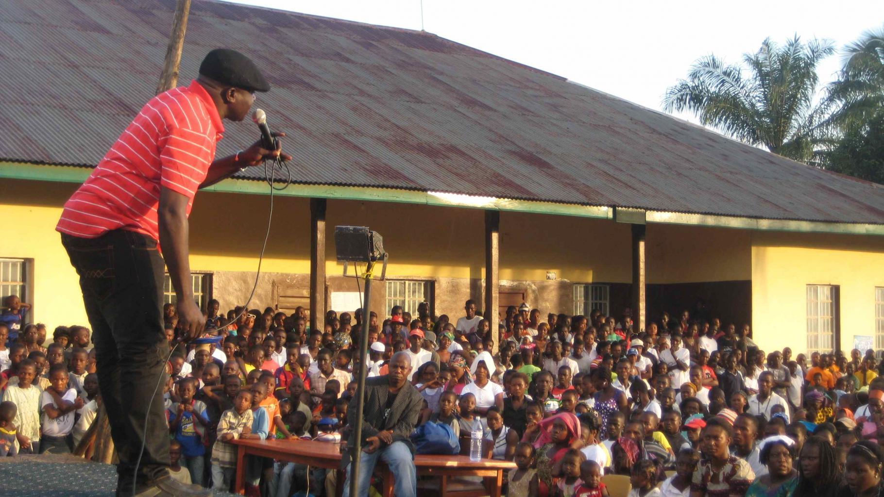 Ein Mann spricht von einer Bühne zum Publikum
