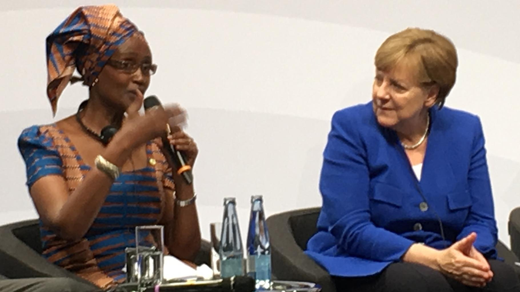 Winnie Byanyima spricht neben Angela Merkel bei einer Podiumsdiskussion.