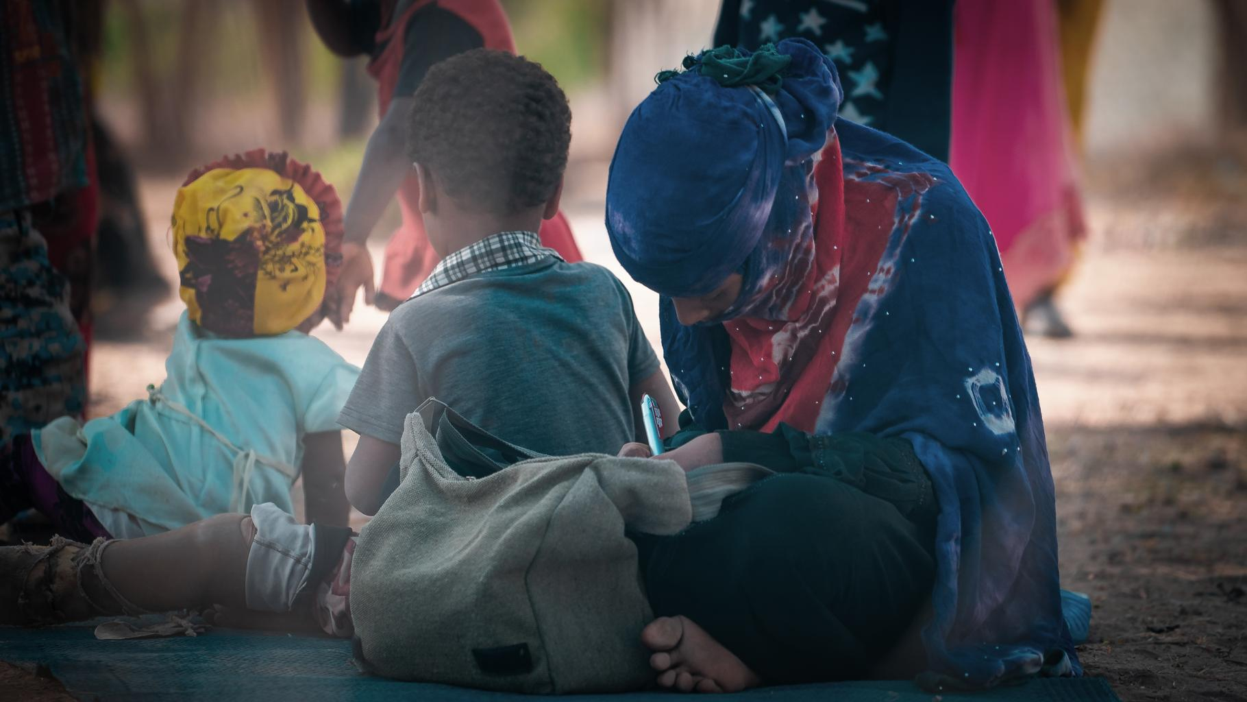 Ein Teenager-Mädchen sitzt neben zwei jüngeren Kindern auf einer Matte und schreibt; eines der Kinder hat eine Bein-Prothese.