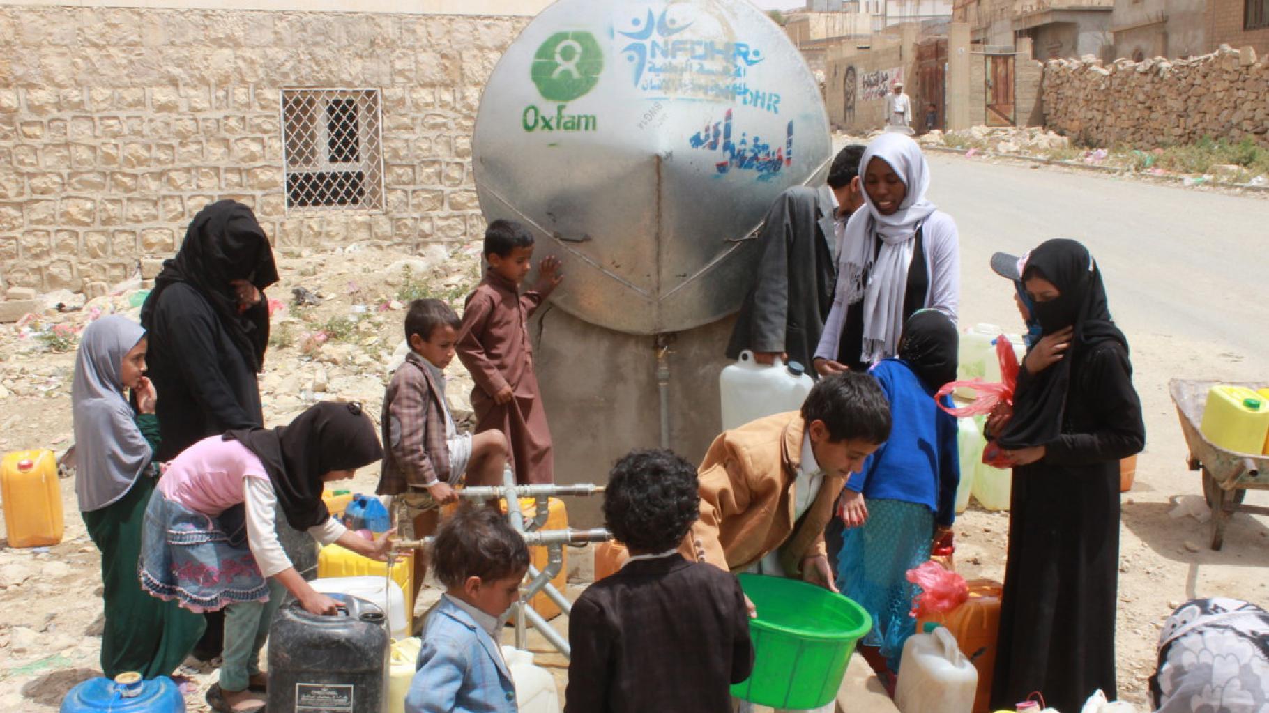 Frauen und Kinder holen Wasser an einem Tank in Khamir im Jemen.