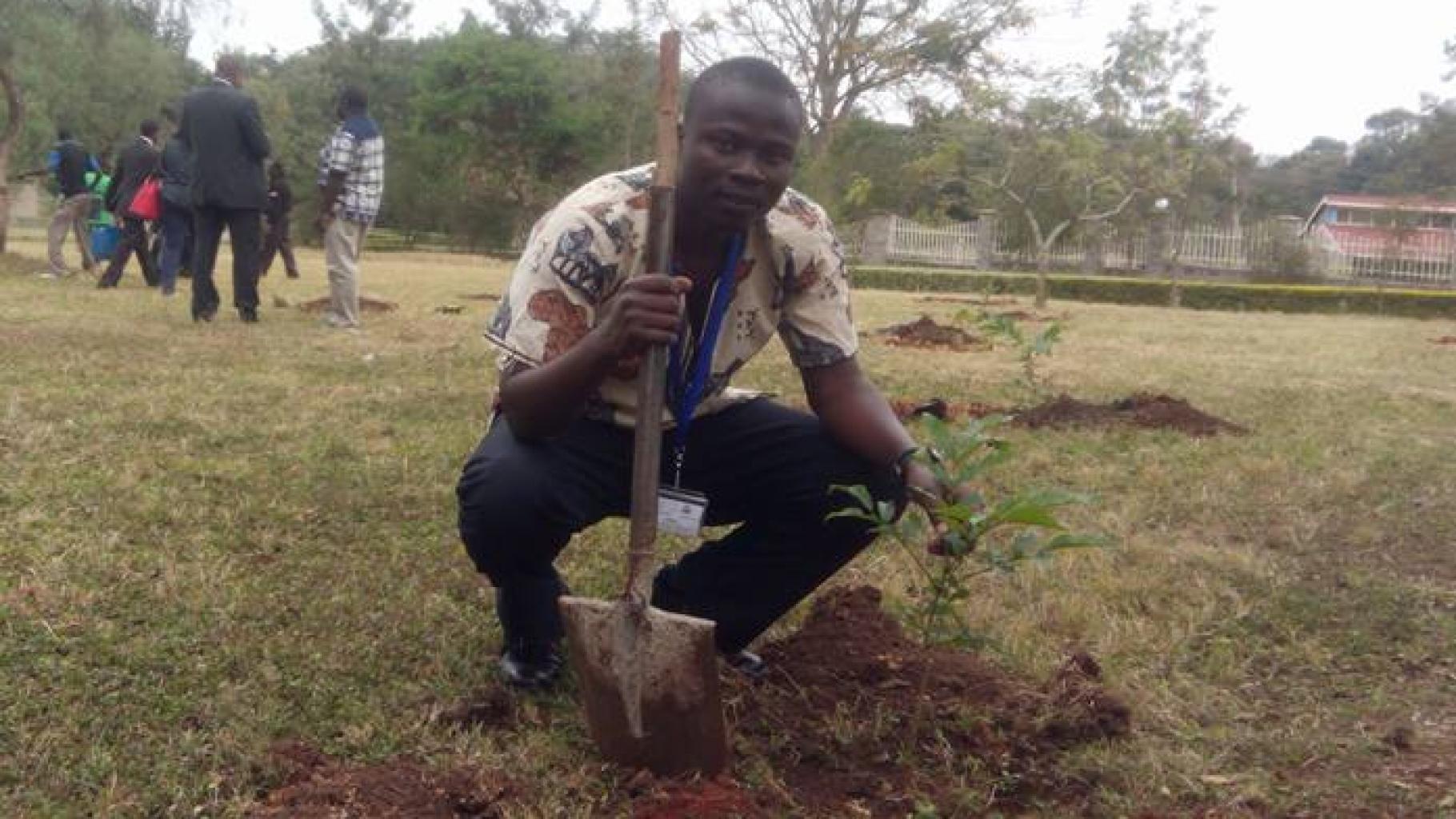 Jonathan Odongo mit einem Spaten neben einem frisch gepflanzten kleinen Baum