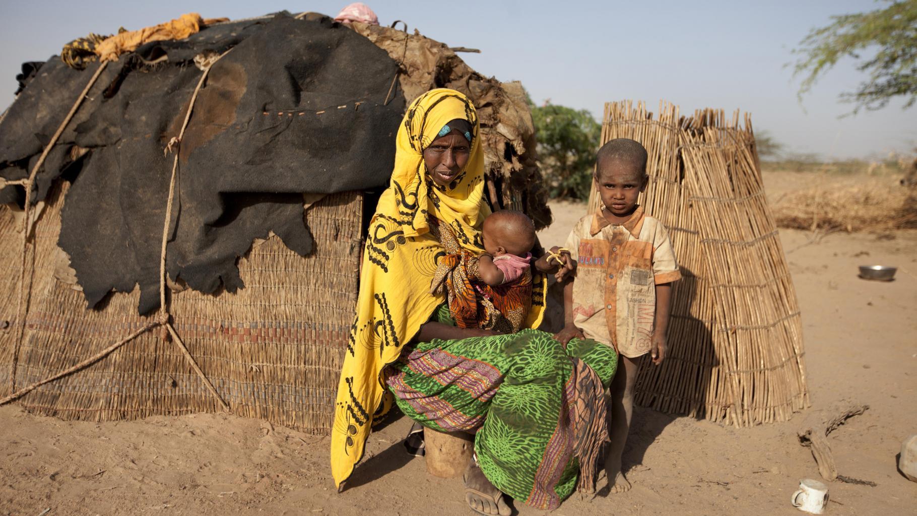Eine Frau sitzt mit einem Baby auf dem Arm vor einer behelfsmäßigen Unterkunft in einer trockenen Landschaft. Ein Junge steht neben ihr.