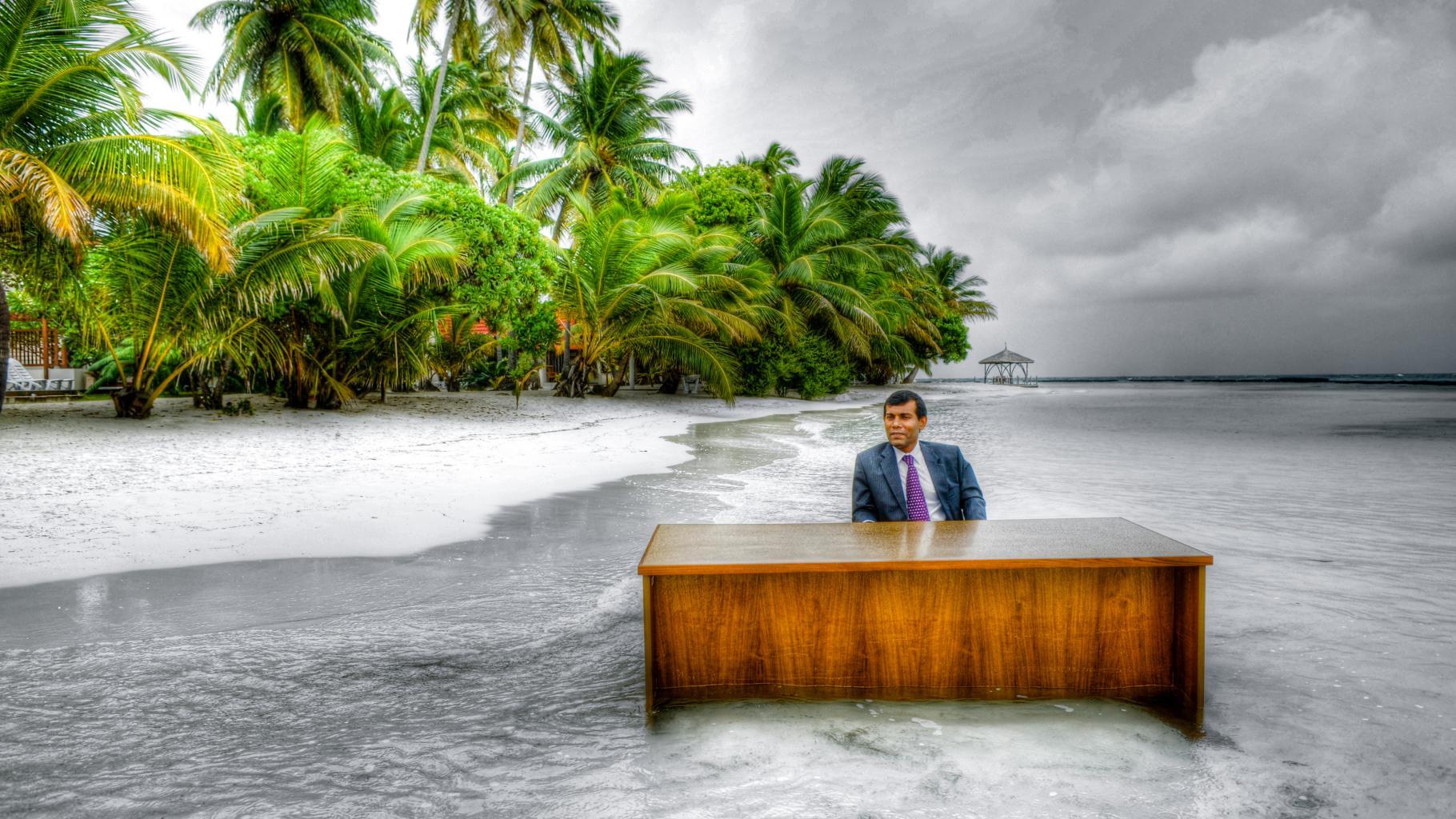 Mohamed Nasheed sitzt im Anzug an einem Schreibtisch – im Meer.