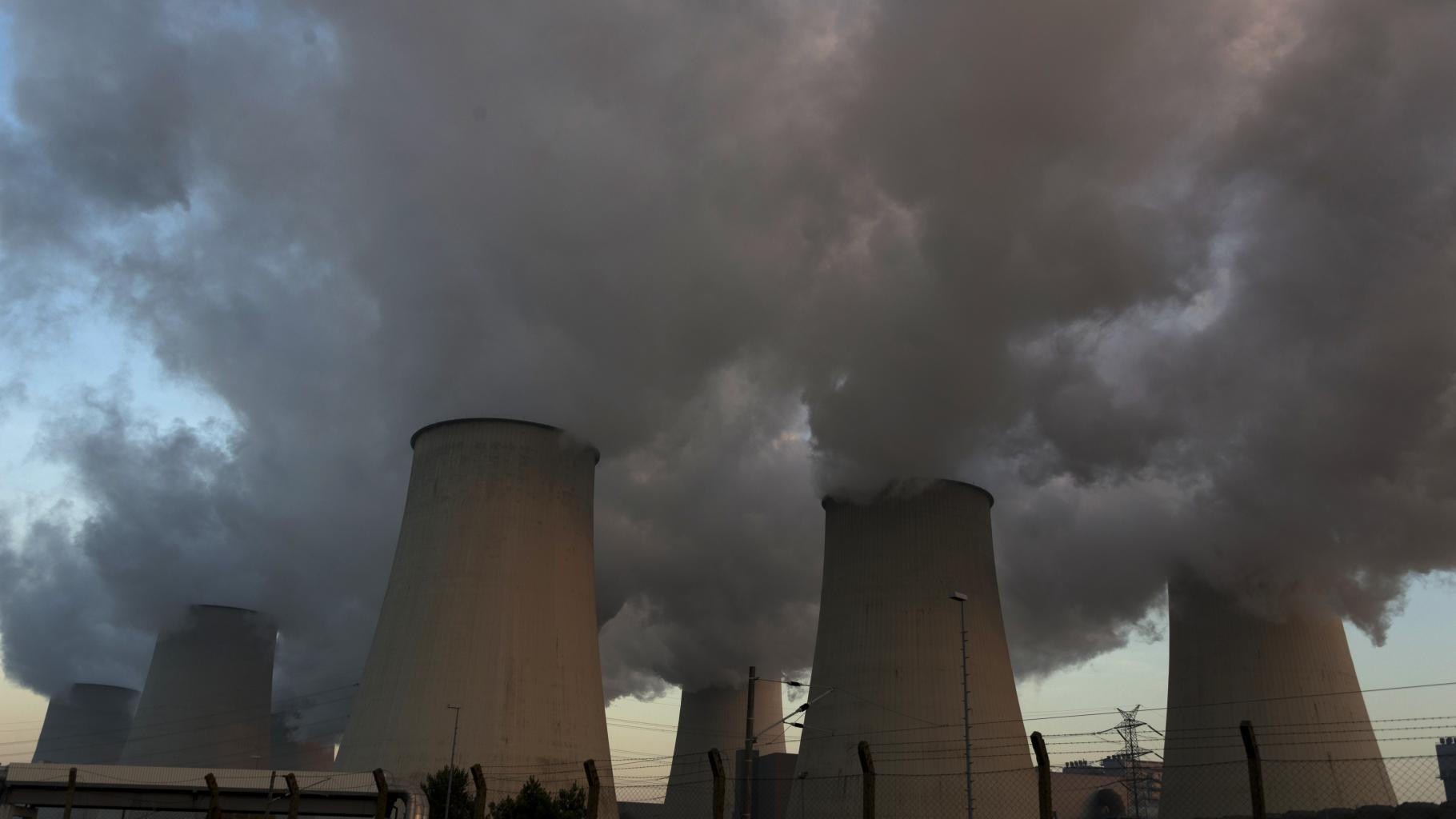 Dampf steigt aus sieben Kühltürmen eines Kraftwerks in den Abendhimmel.