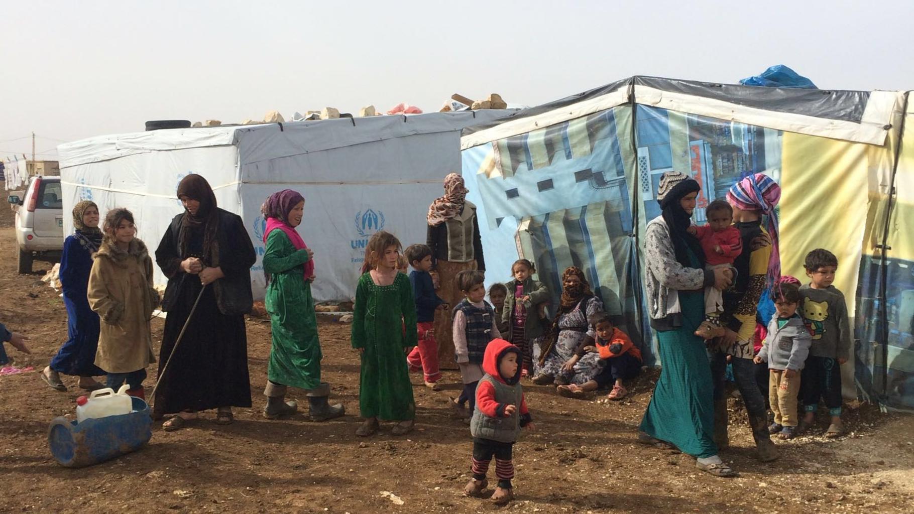 Eine Gruppe von Frauen und Kindern vor Zelten