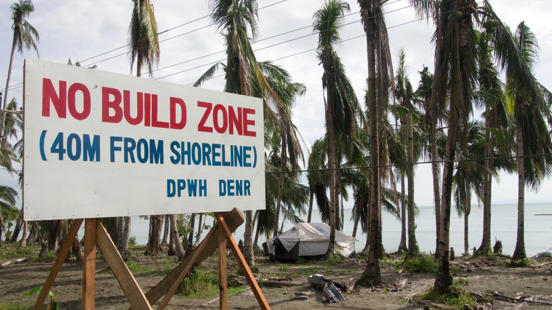 """Ein Schild mit der Aufschrift """"No build zone (40m from shoreline) DPWH DENR"""" steht an einer Küste. Im Hintergrund sind umgeknickte Palmen, ein Zelt und das Meer zu sehen."""
