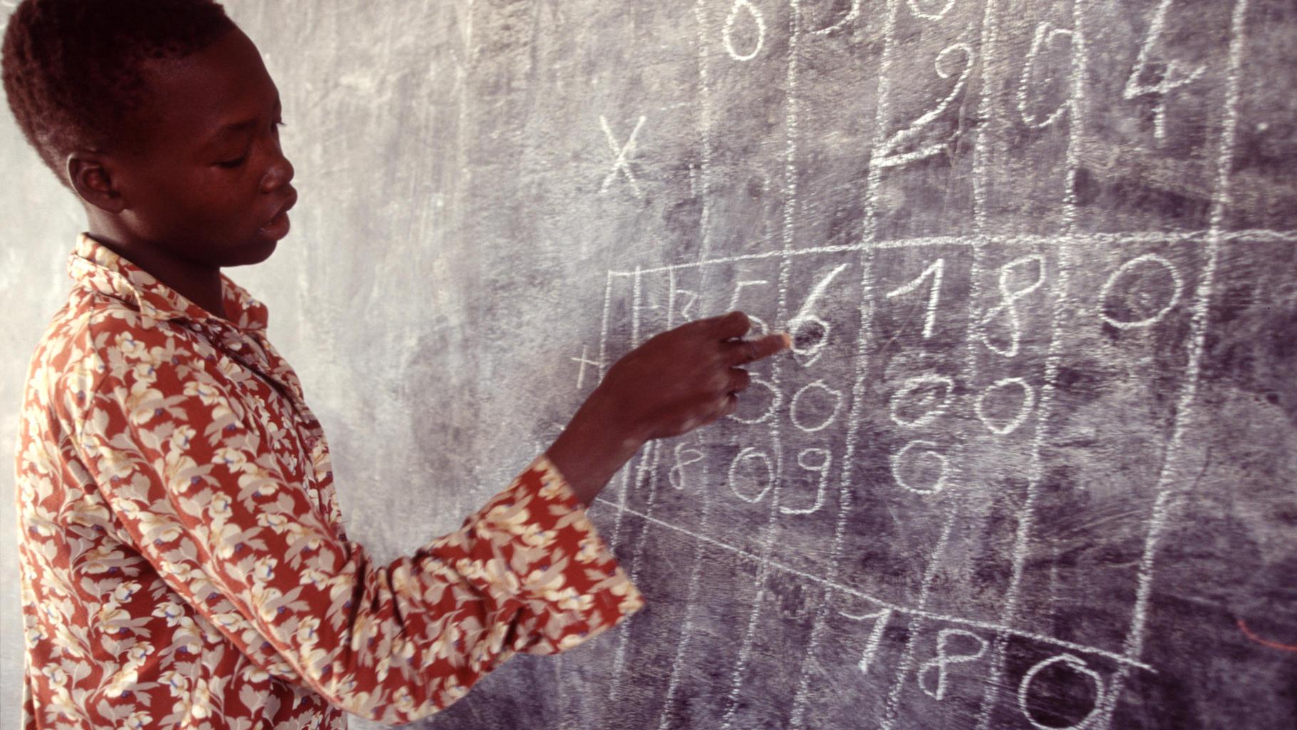 Ein Lehrer erklärt schriftliches Multiplizieren an der Tafel