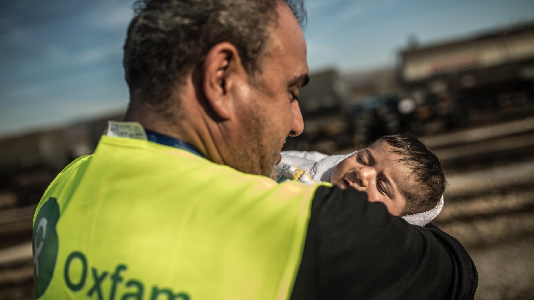 Oxfam-Mitarbeiter hält ein Baby in Mazedonien