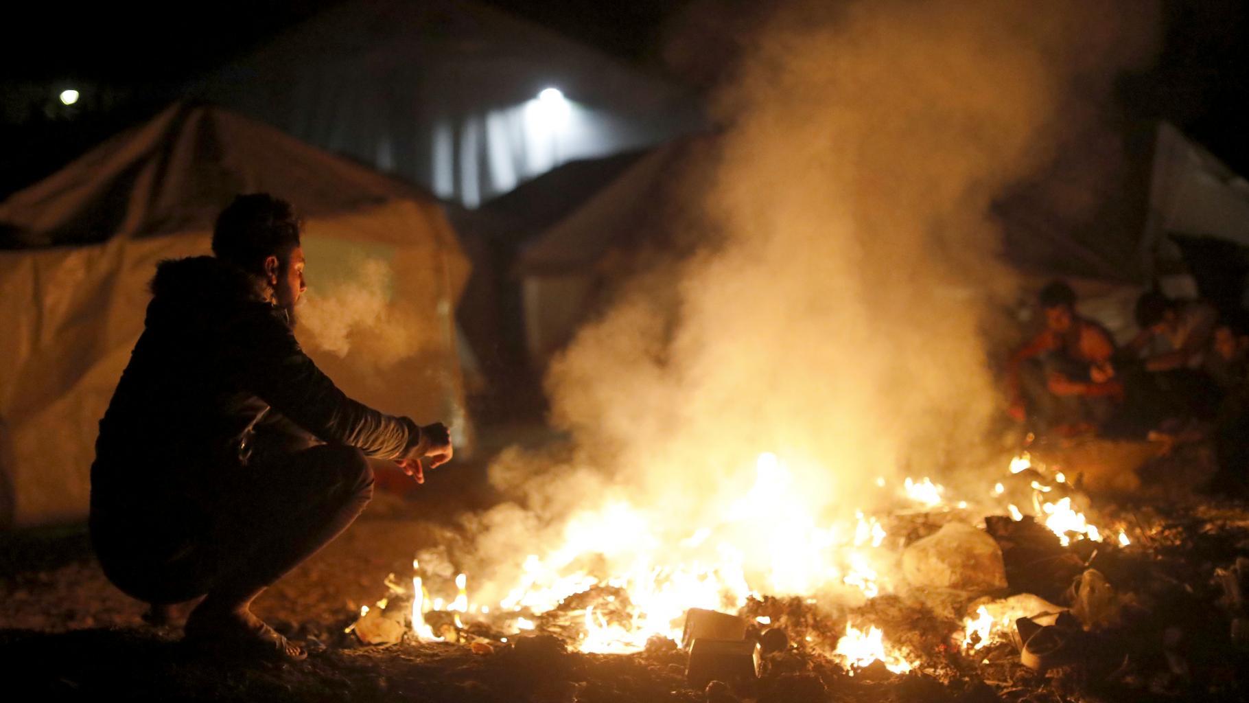 Geflüchteter in Griechenland vor einem Feuer