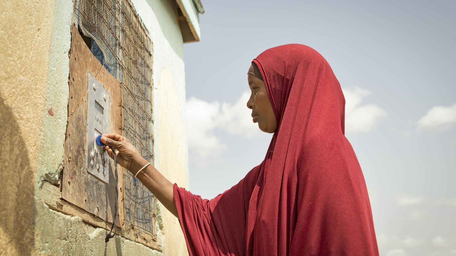 Arron Gesar hält ihren Chip gegen den Sensor des Wasser-Automaten, um Trinkwasser zu holen.