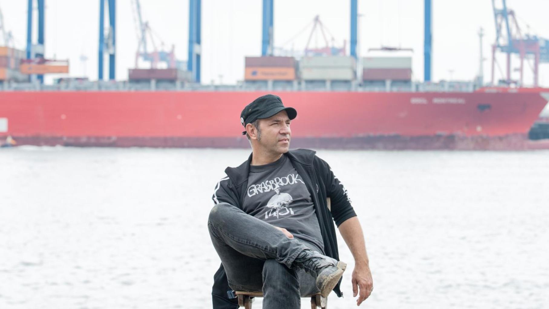 Ole Plogstedt sitzt vor einem Containerschiff