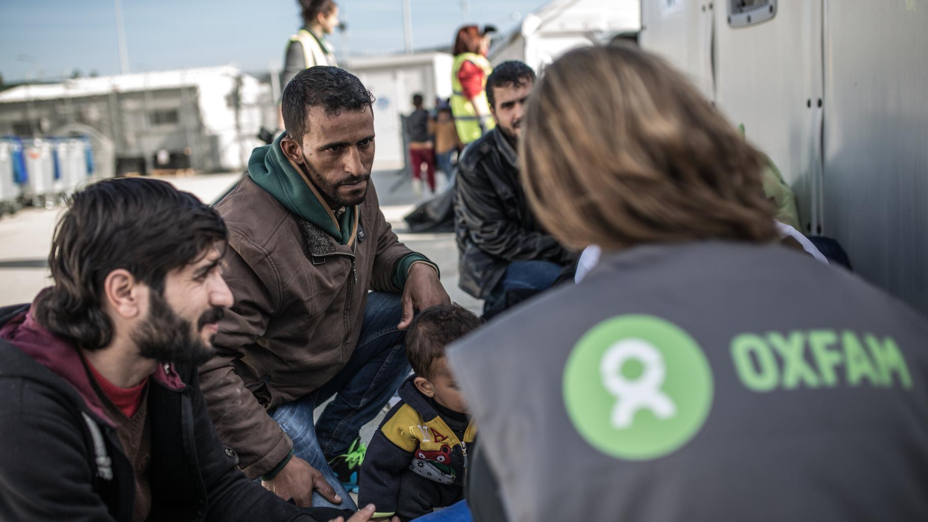 Eine Frau mit Oxfam-Weste, Rücken zur Kamera, spricht mit einer Familie in einem Flüchtlingscamp.