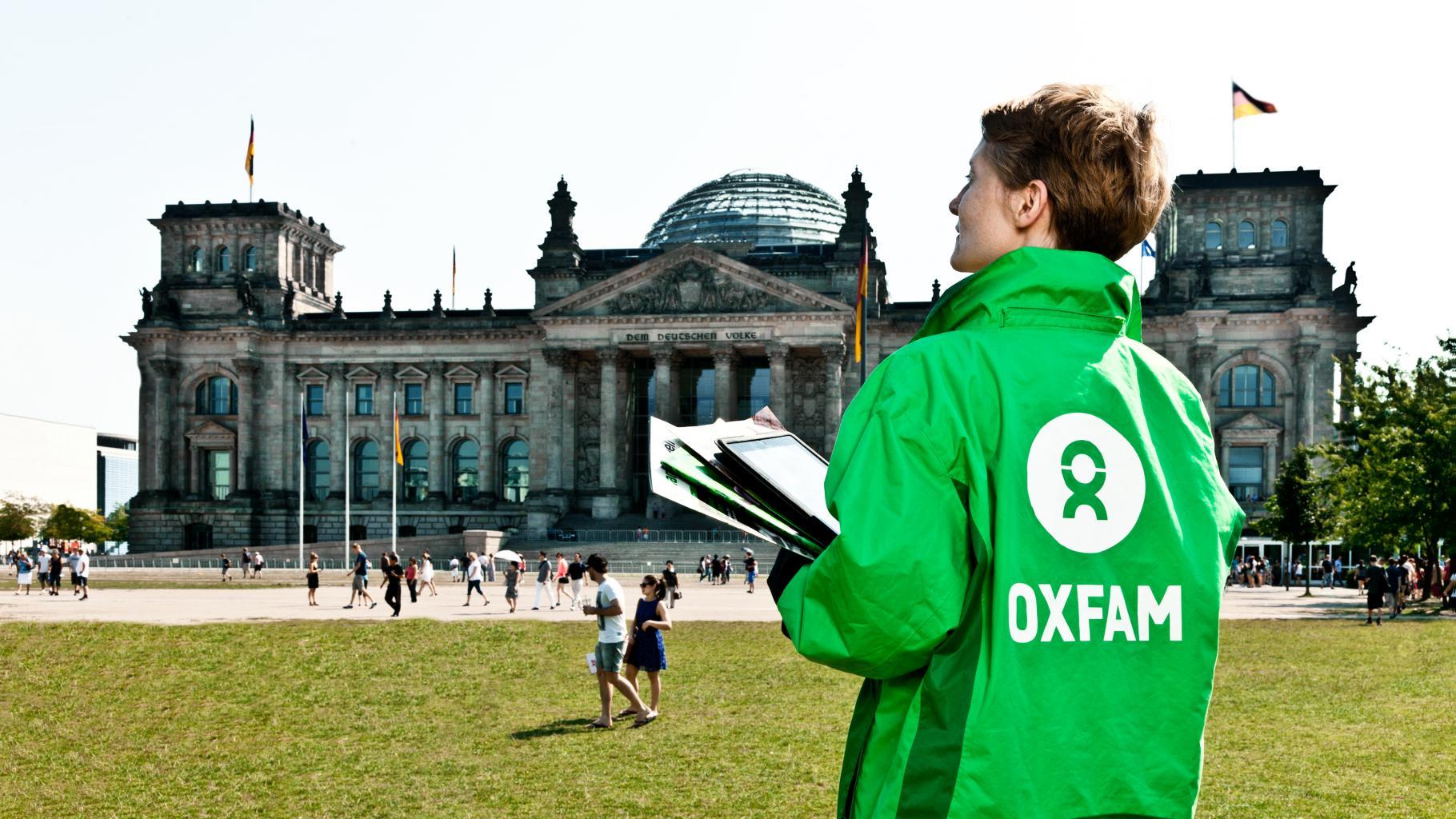 Eine Aktivistin in Oxfam-Jacke steht vor dem Reichstagsgebäude