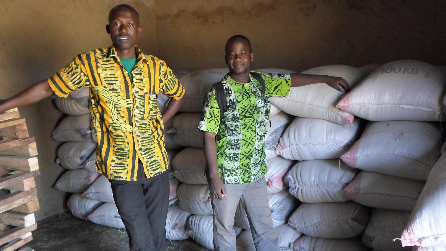 Männer stehen im Getreidespeicher vor Getreidesäcken
