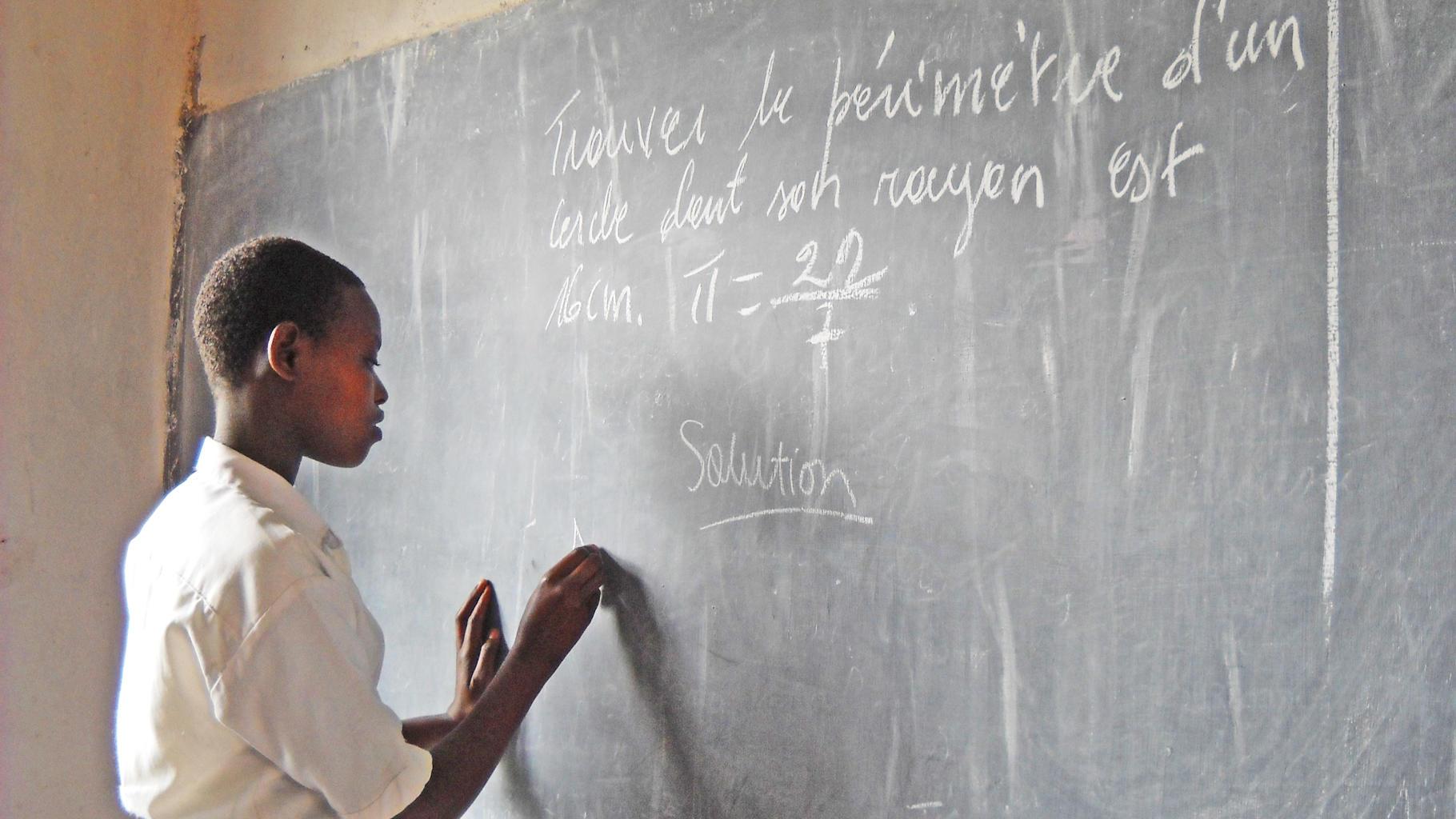 Schülerin löst Mathe-Aufgabe an der Tafel
