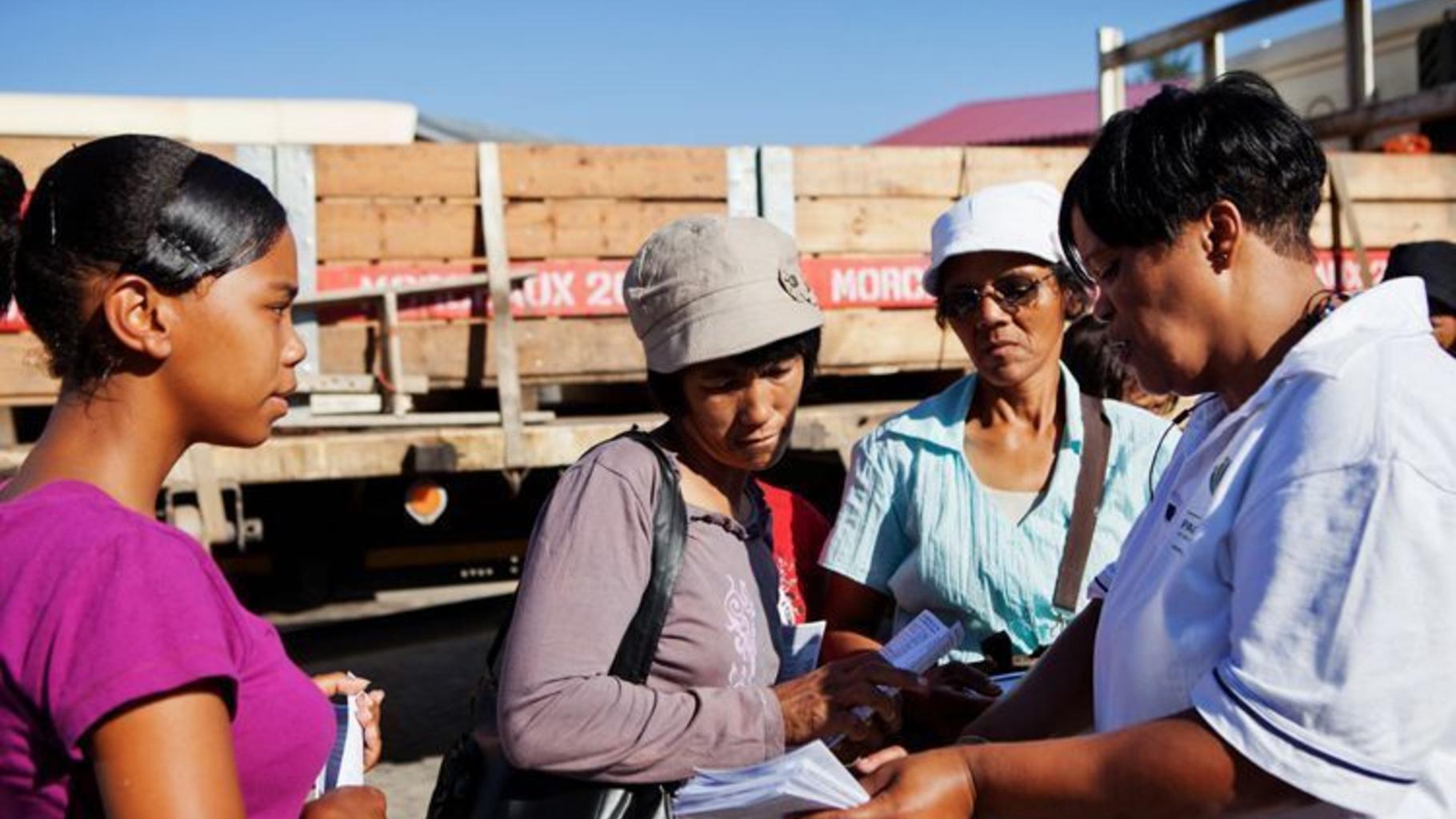 Frauen erhalten Informationsmaterial zu ihren Arbeitsrechten.