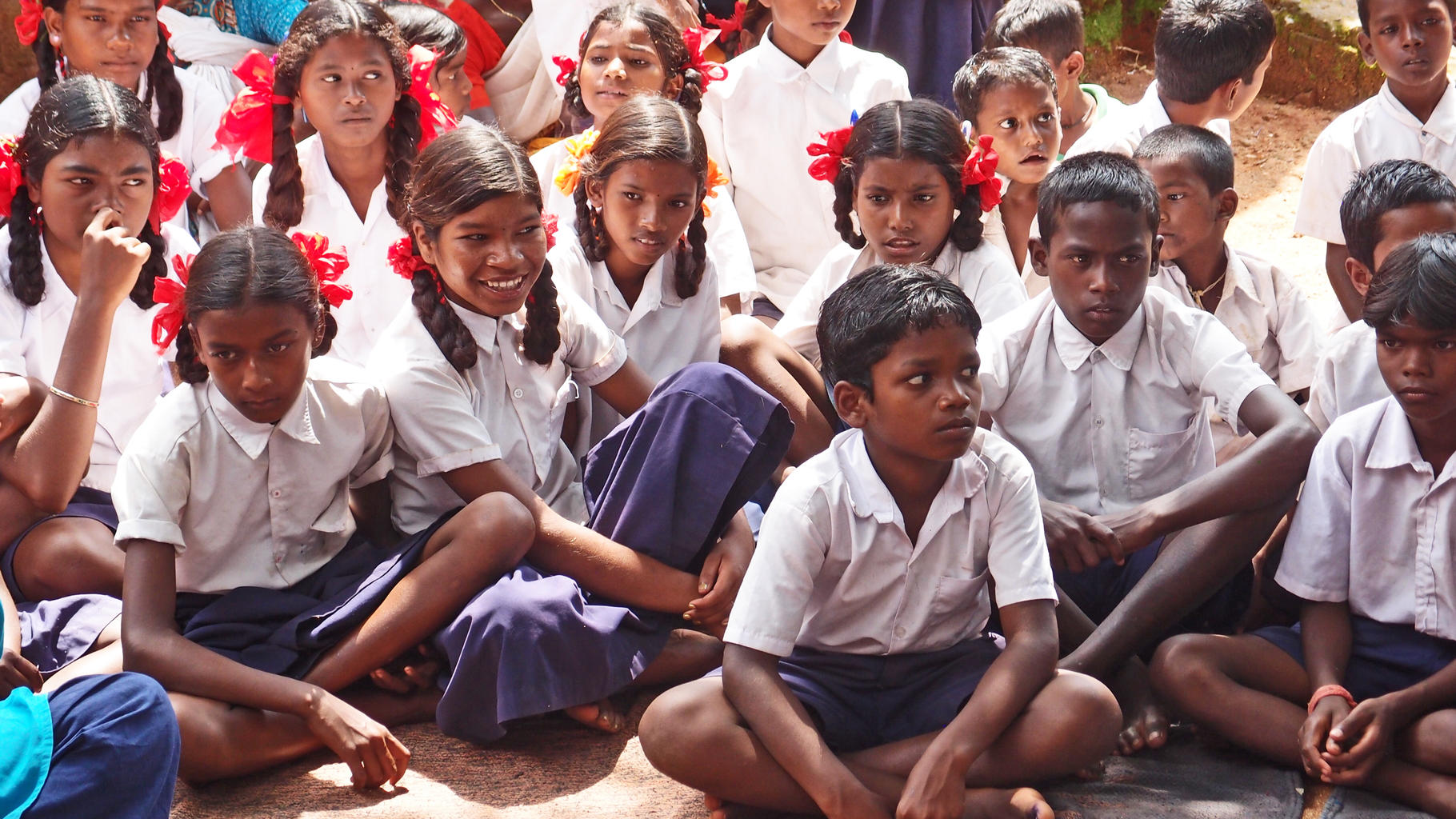 Schüler/innen sitzen auf dem Boden
