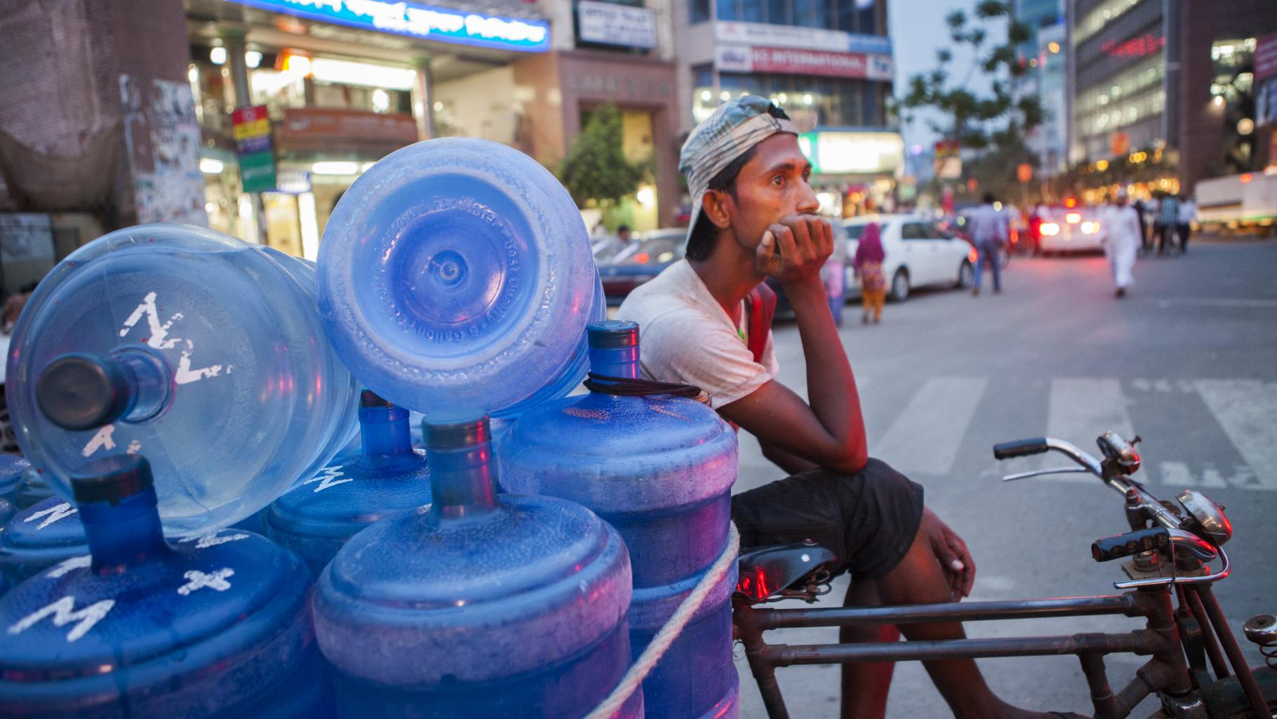 Ein junger Mann sitzt wartend mit leeren Wasserkanistern am Straßenrand.