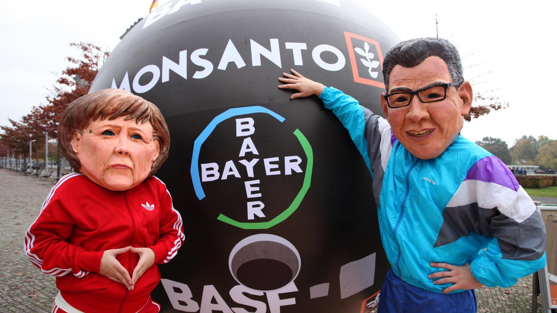 In Trainingsanzüge gekleidete Aktivist/innen mit Masken von Angela Merkel und Gerd Müller posieren neben einer sie überragenden Bowlingkugel mit den Logos von Monsanto, Bayer und BASF.