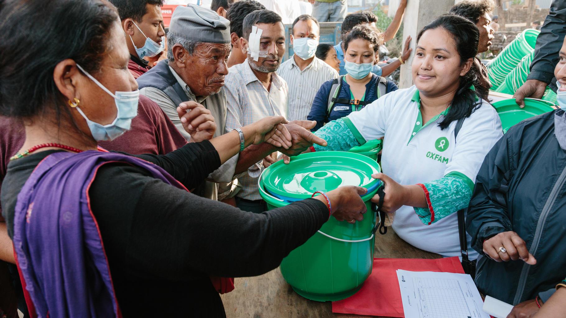 Frau verteilt Hygienesets mit Eimern, Handtüchern und Seife