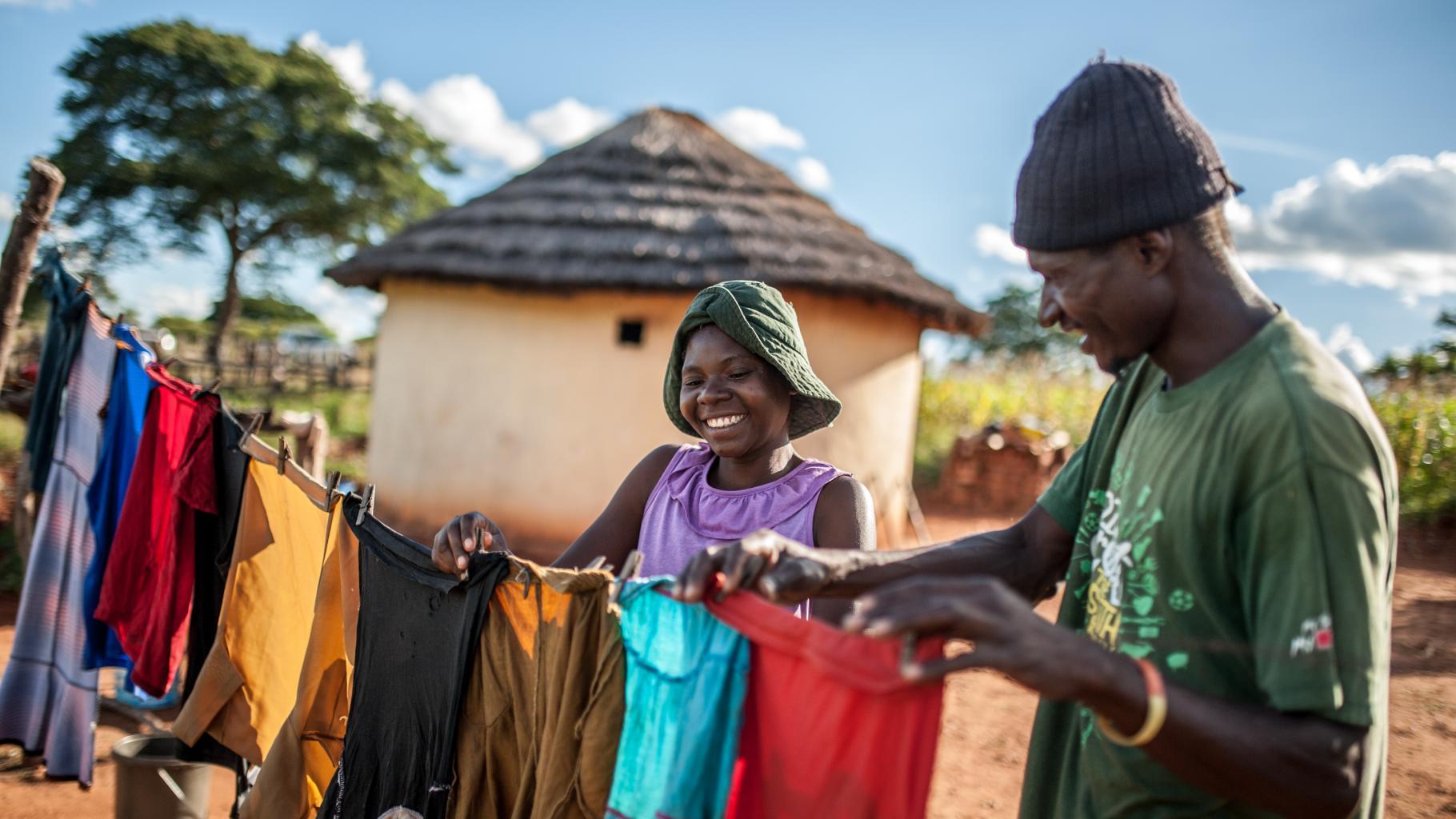 Eine Frau und ein Mann hängen Wäsche auf