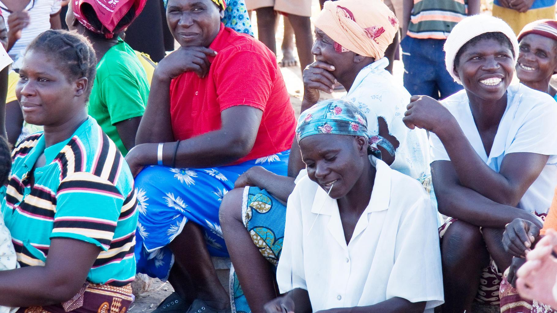 Frauen sitzen am Boden und schauen ein Theaterstück
