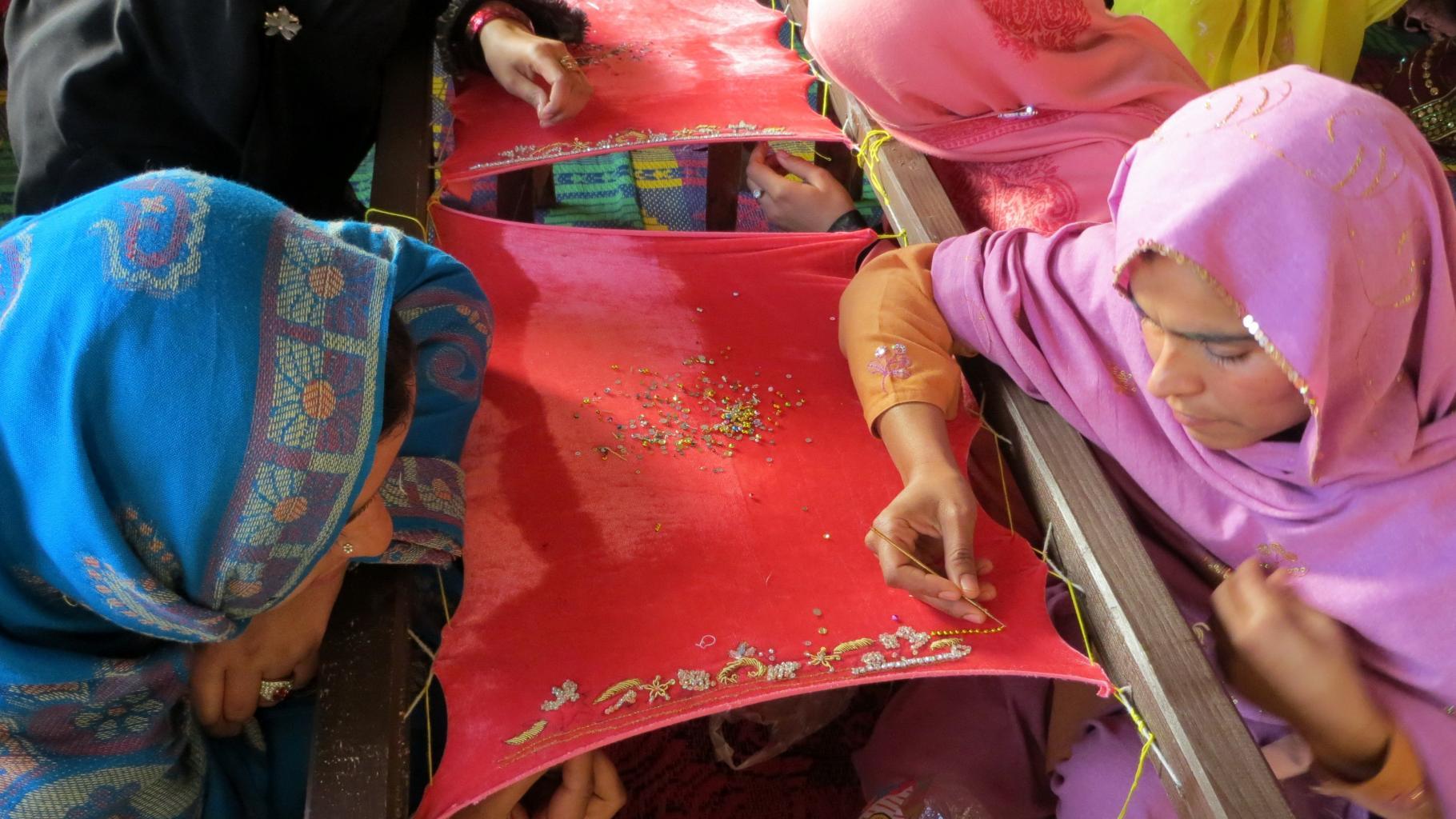 Vier Frauen sitzenumd einen Stickrahmen und bearbeiten zu zweit ein zu bestickendes Tuch