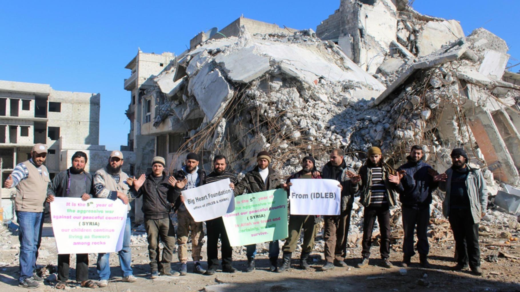 Eine Gruppe von Männern steht vor Trümmern eines Gebäudes. Sie reichen sich die Hände und zeigen Transparente.