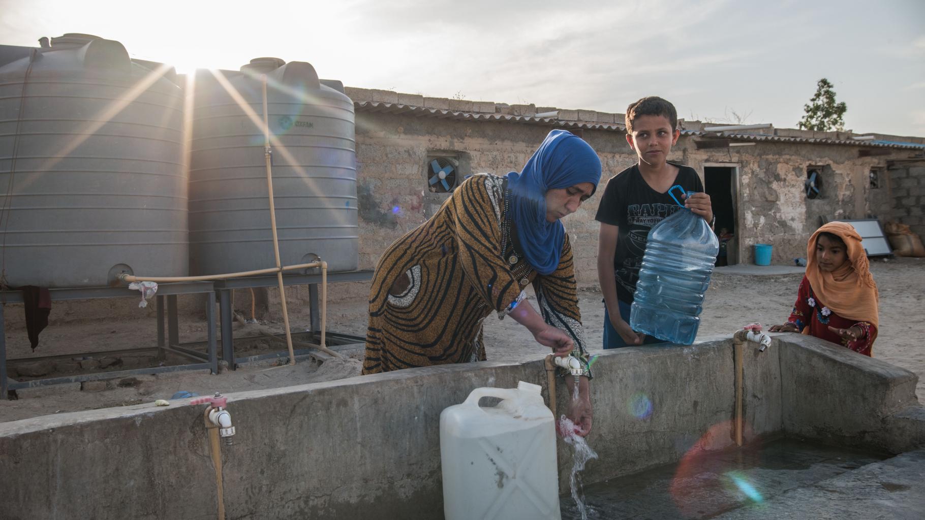 Eine Frau mit zwei Jungen füllt Wasserkanister an einem Wasserhahn auf. Im Hintergrund sind zwei Wassertanks und ein altes verlassenes Hauss zu sehen.