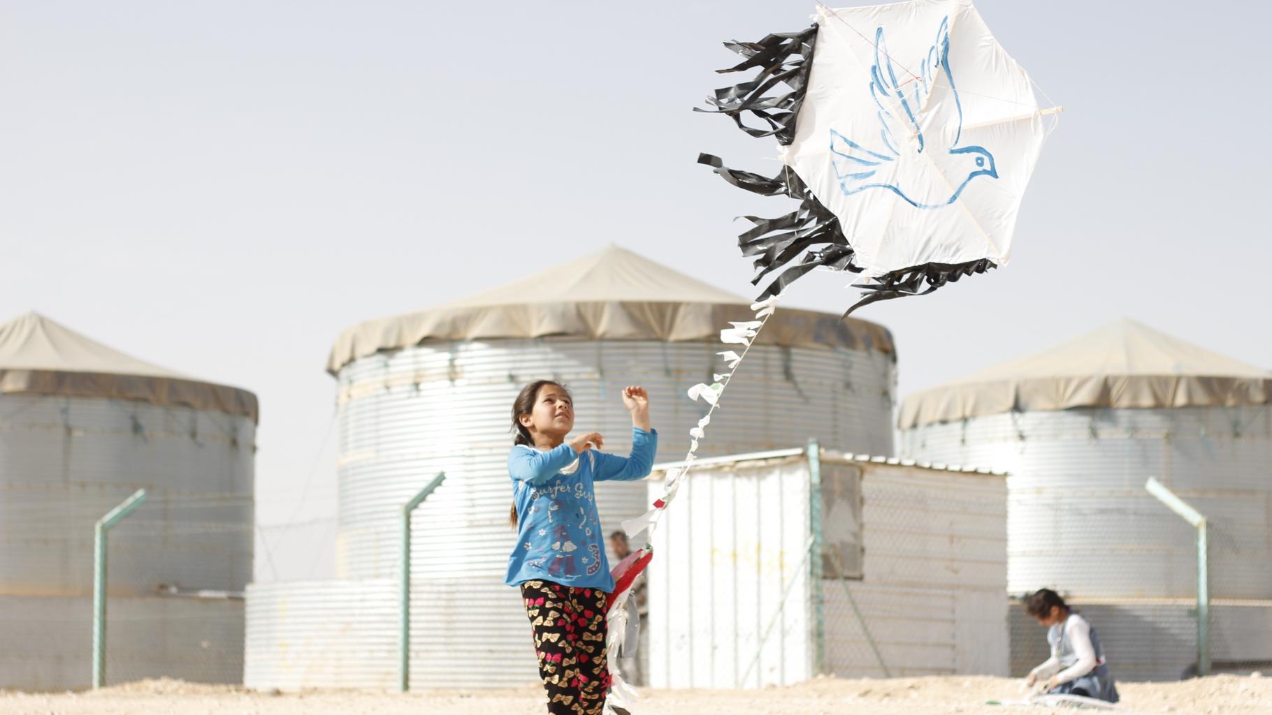 Mädchen mit Drachem im Flüchtlingscamp Zaatari. Auf dem Drachen ist eine Friedenstaube aufgemalt.