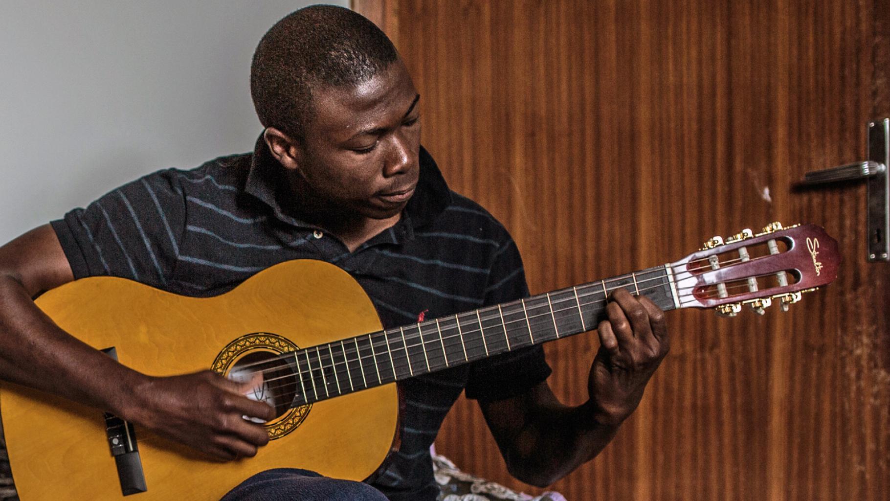 Der nigerianische Flüchtling Peter Okharedia spielt Gitarre