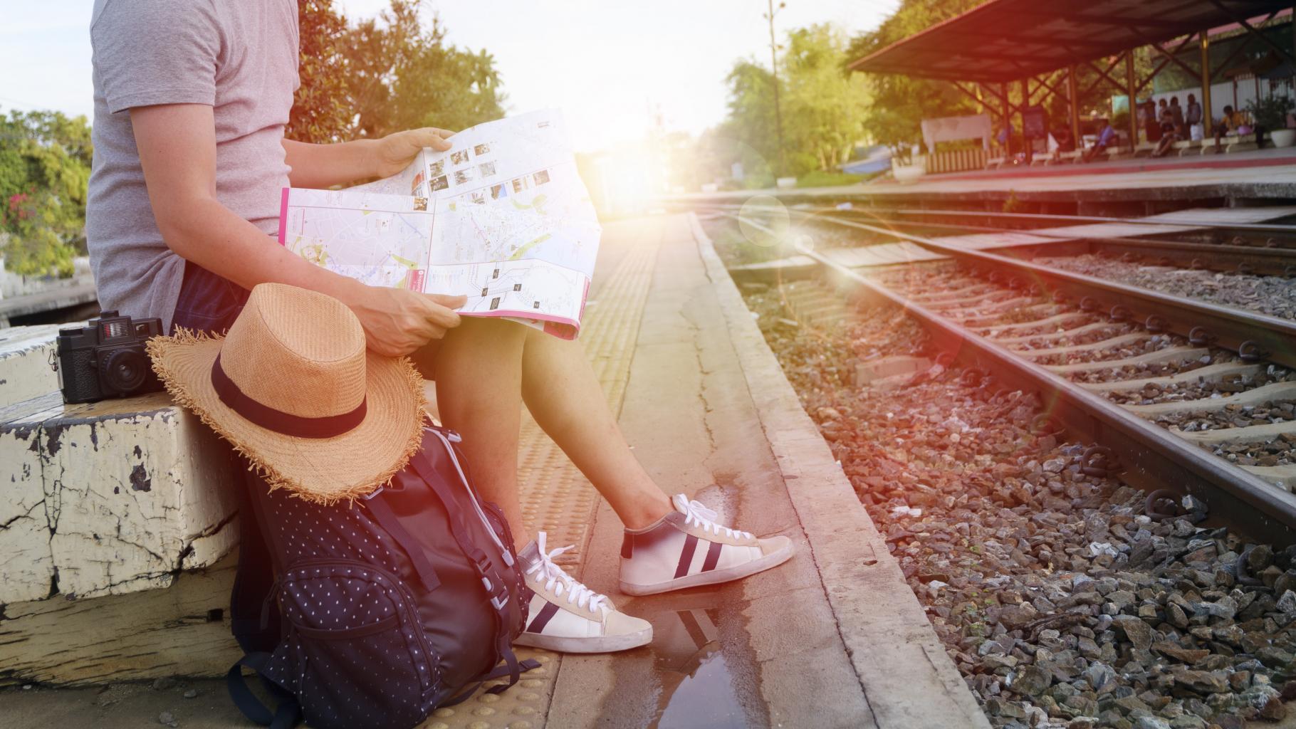 Ein Mann sitzt nebst Rucksack, Kamera und Strohhut an einem Bahnsteig und studiert eine Karte.
