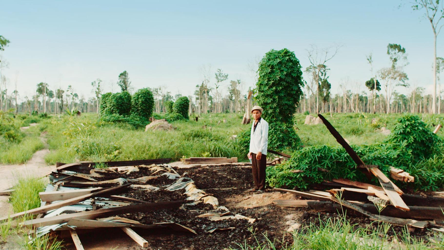Ein vom Landraub Betroffener auf den Trümmern seines zerstörten Hauses.