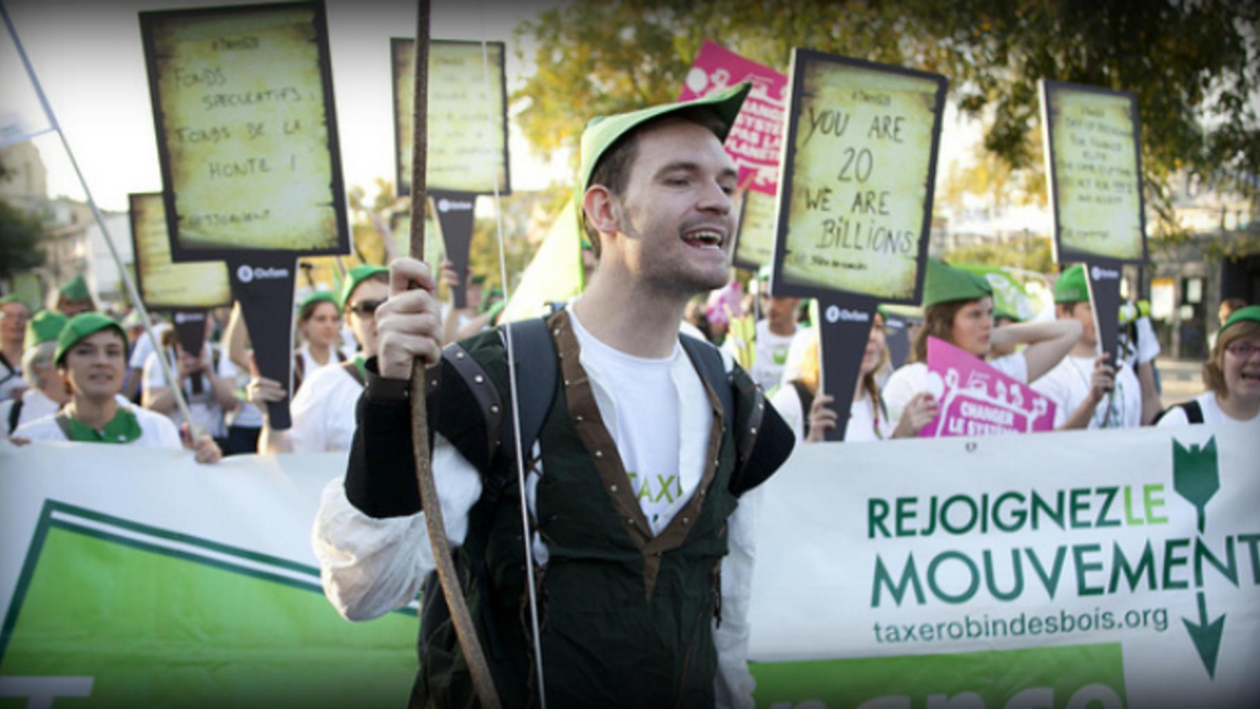 Robin Hood im Demozug vor Banner