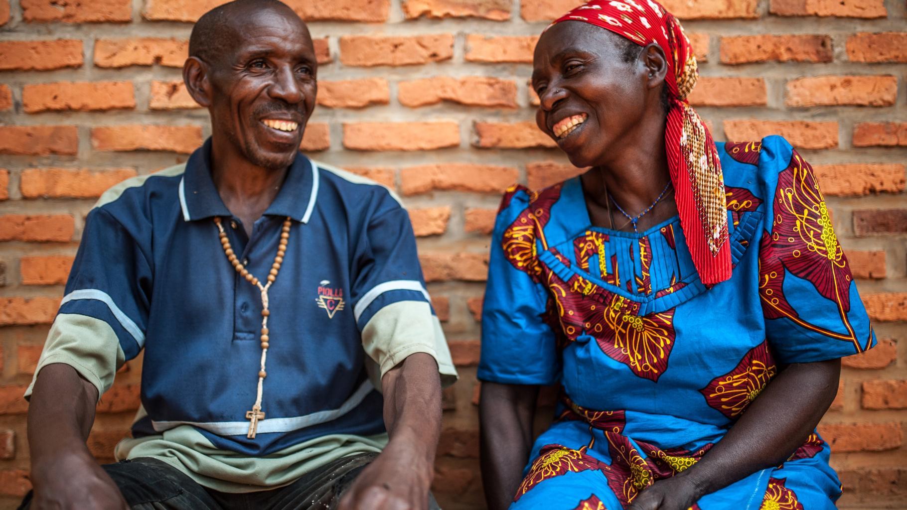 Ein Mann und eine Frau sitzen lachend vor einer Backsteinwand.