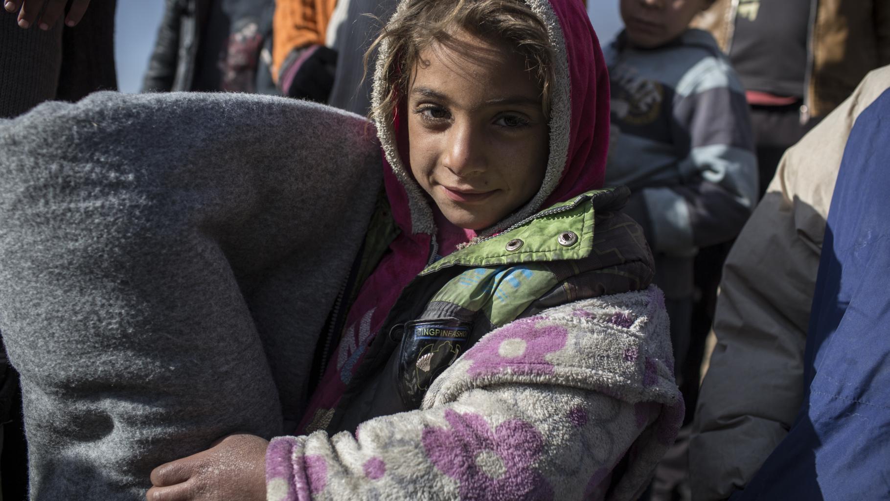 Mädchen hält eine graue gerollte Decke im Arm.