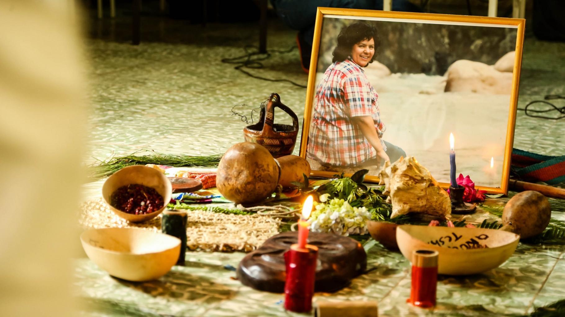 Ein Schrein mit einem kleinen Foto von Berta Cáceres und Kerzen, Blumen, Schalen und anderen kleinen Gegenständen