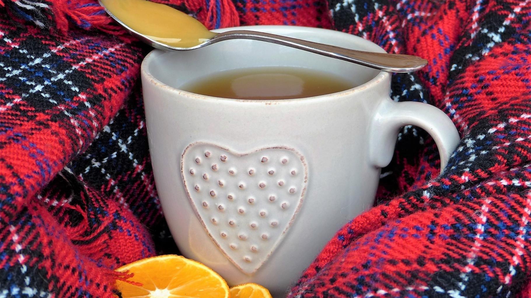 Eine Tasse Tee mit einem Löffel Honig und Orangenscheiben