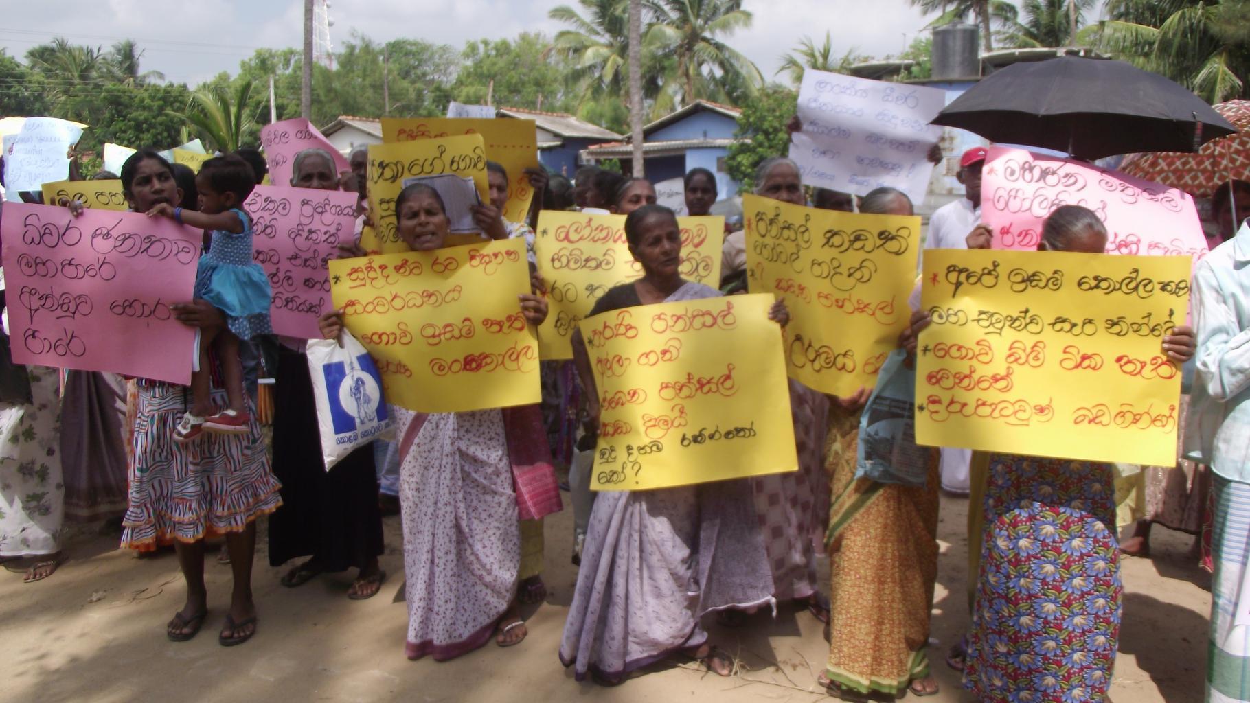 Frauen und Männer protestieren mit Schildern gegen Landraub