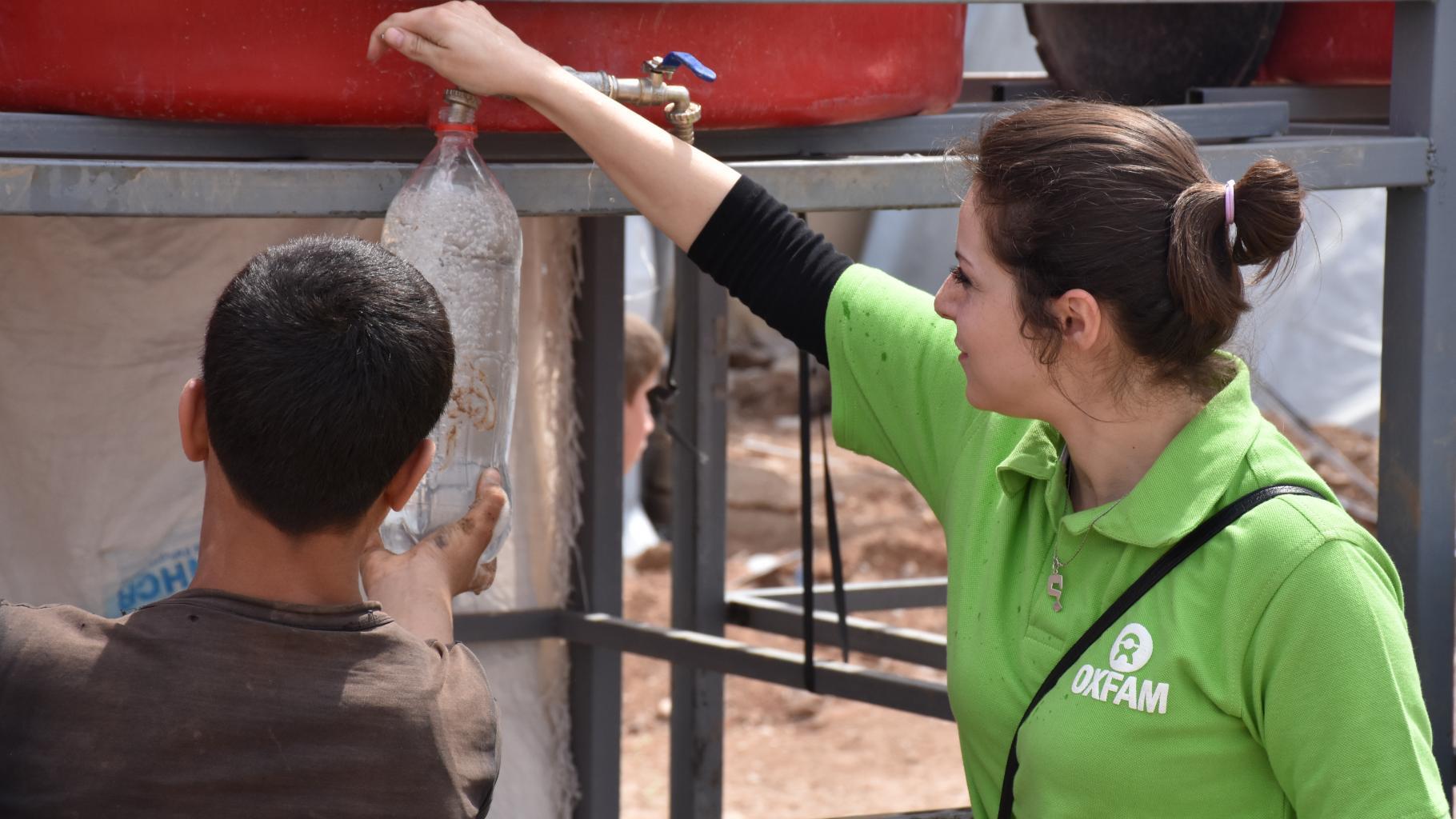 Eine Oxfam-Mitarbeiterin hilft einem Kind, eine Wasserflasche aus einem Tank zu füllen.