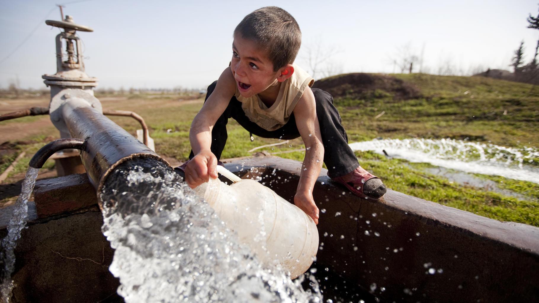 Kleiner Junge spielt am Brunnen